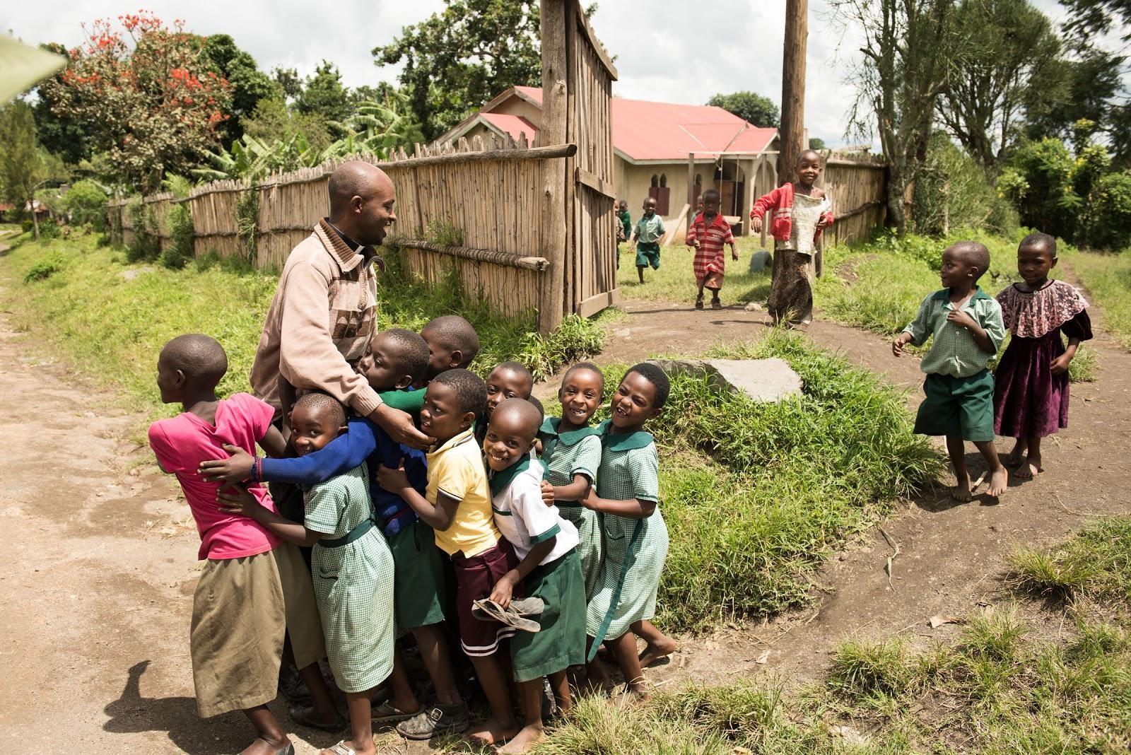 Fig. 1:     Father Sylvanus and the children of Kidubuli      © Keena Photo