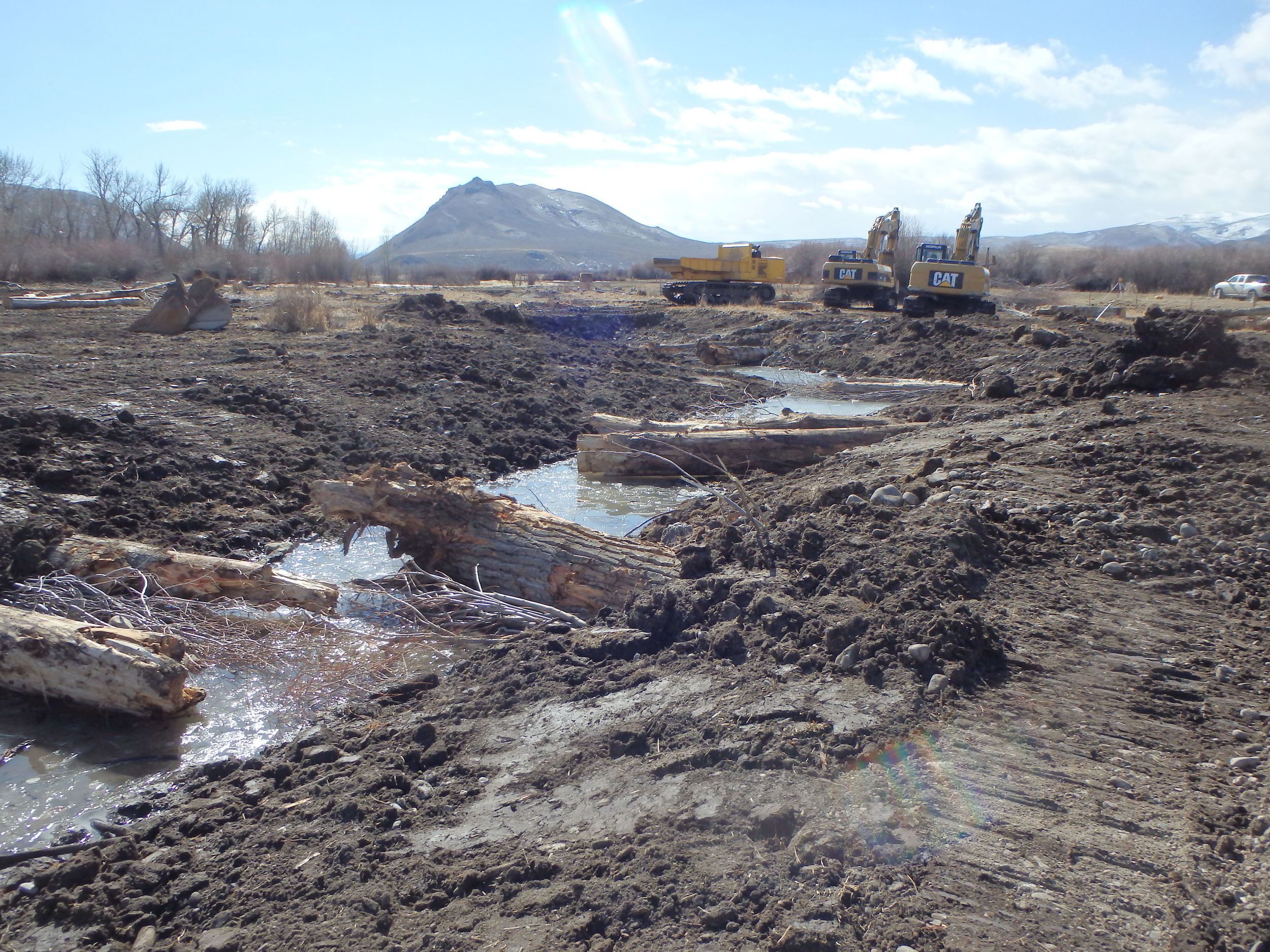 Stream Restoration installing cover logs in a newly created backwater channel