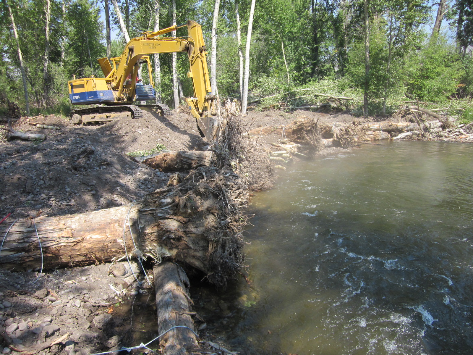 During construction - the first toe-logs and logs with rootwads are installed and secured