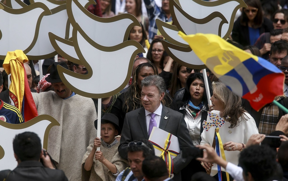 Colombian President, Juan Manuel Santos, holds a copy of the final text of the peace agreement with the FARC guerrillas