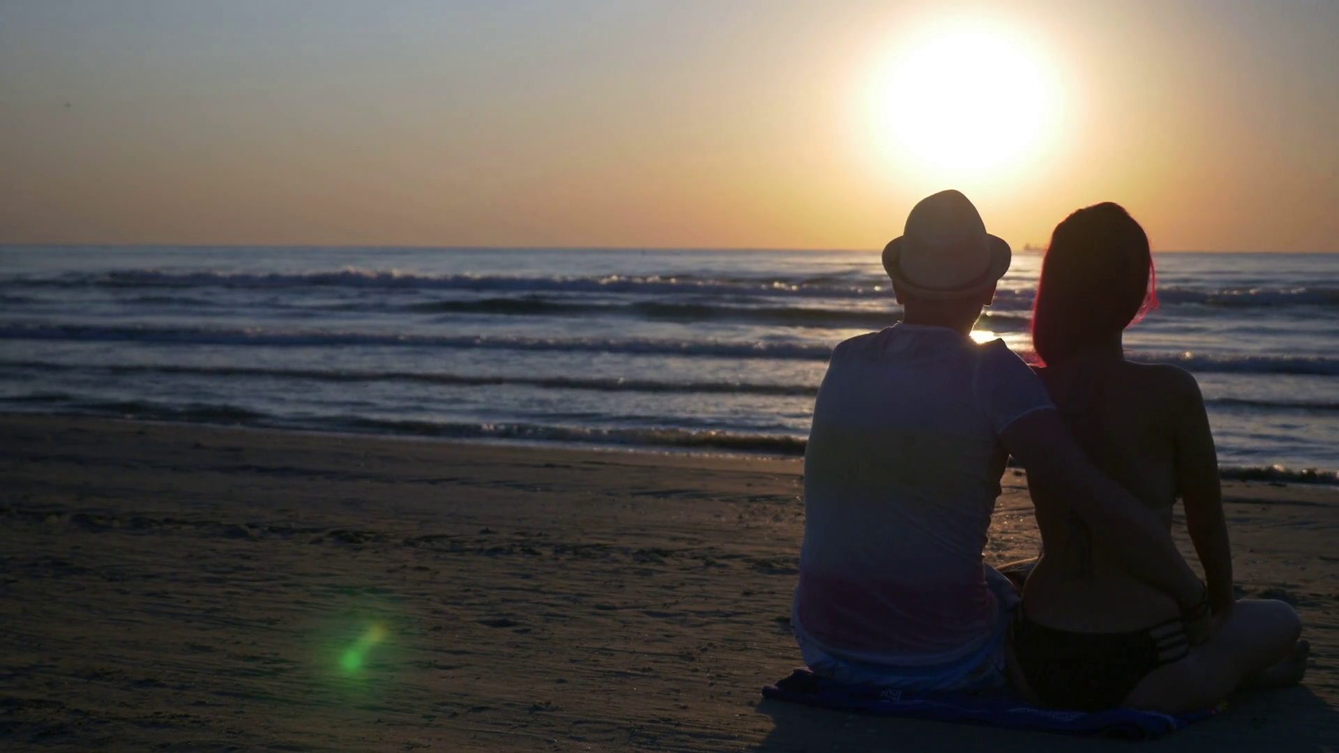 romantic-couple-sitting-on-the-beach-hugging-and-kissing-at-sunrise_s8x5sg7ue_thumbnail-full01.png
