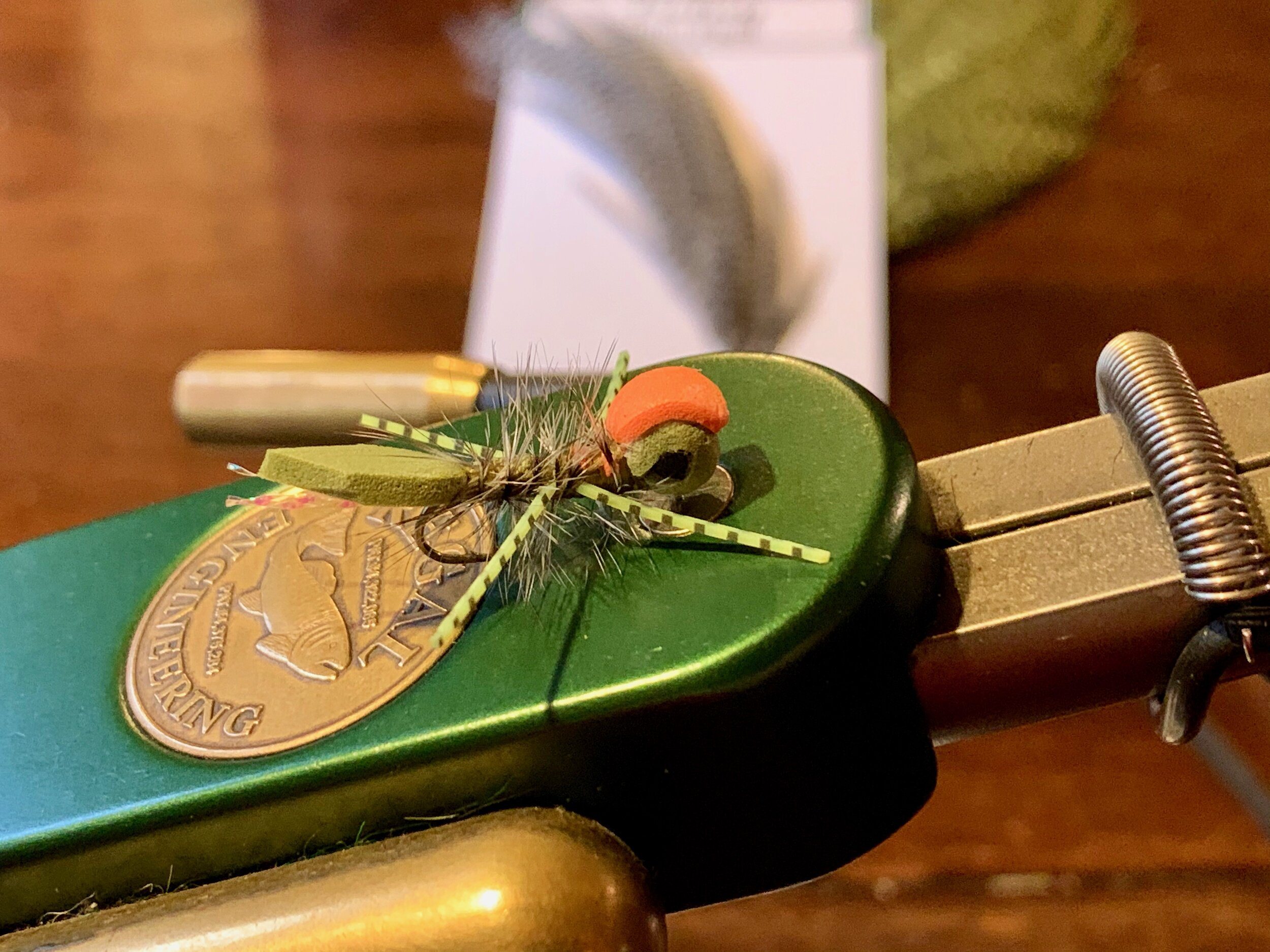 A Micro Gurgler tied in olive with black foam eyes and an orange indicator.