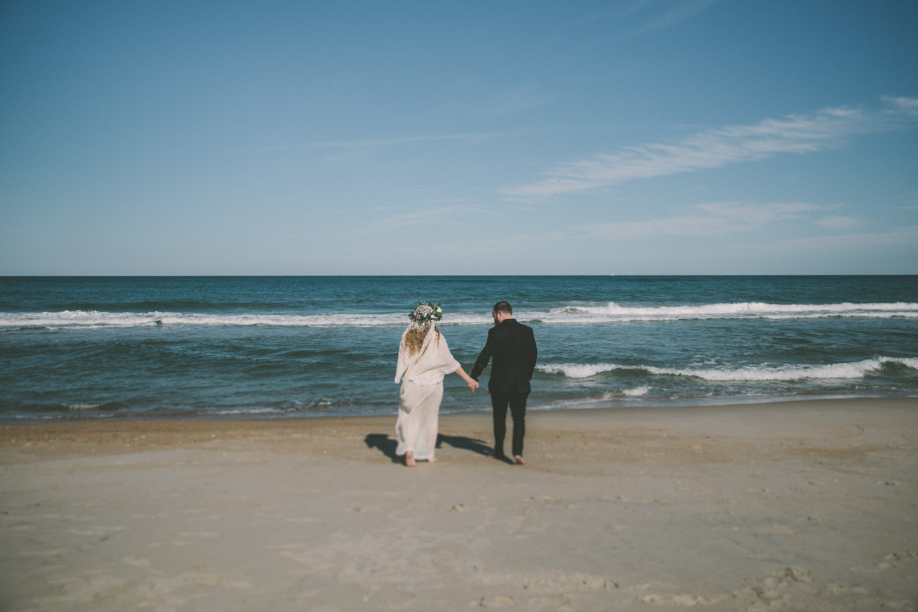 bride and groom walking to the ocean.jpg