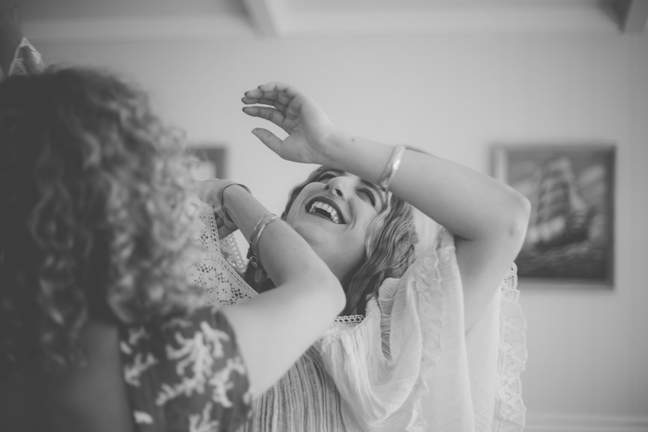 bride laughing getting her dress on.jpg