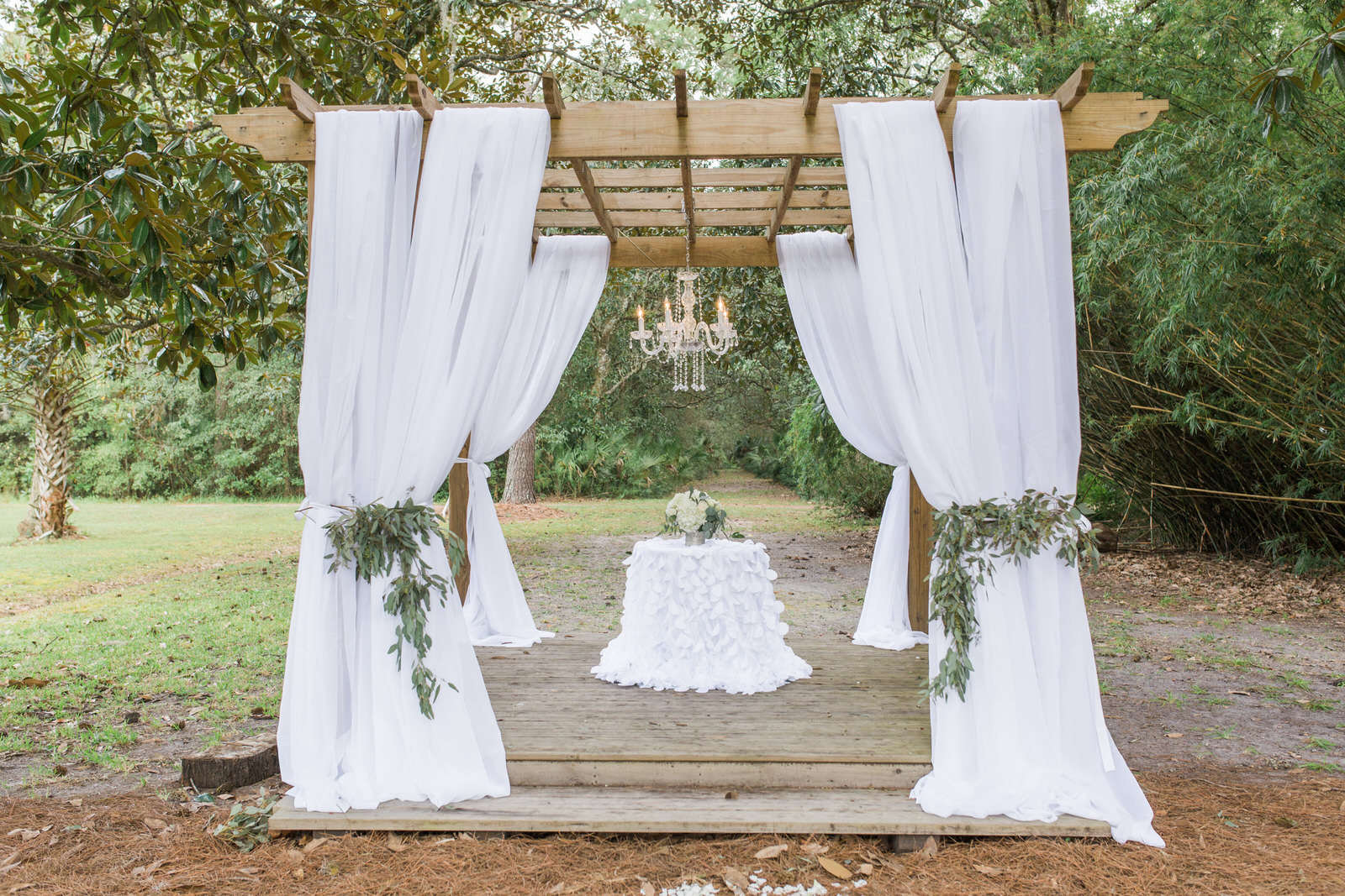 Gazebo draped in white fabric and accented with eucalyptus for wedding ceremony at The Linwood outside of Jacksonville