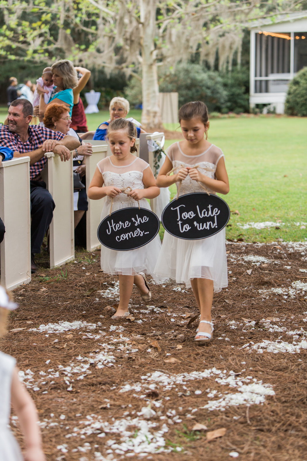 Flower girls carrying signs during wedding ceremony
