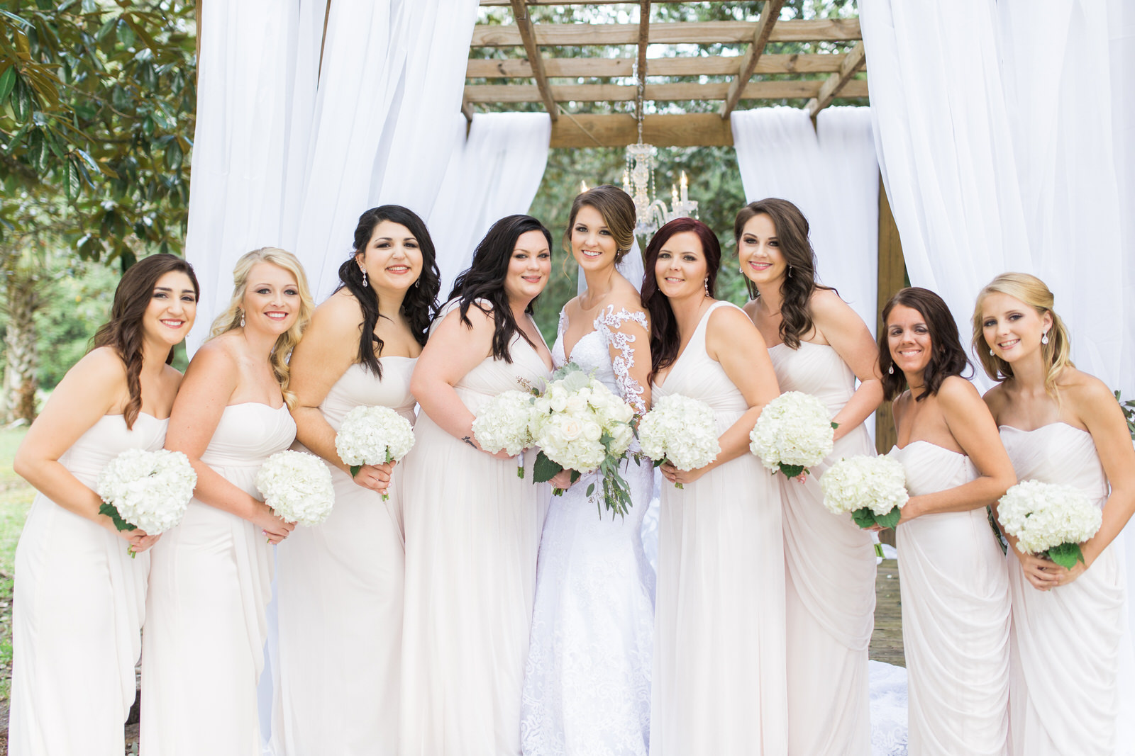 Bride with her bridesmaids in cream colored dresses, white bouquets