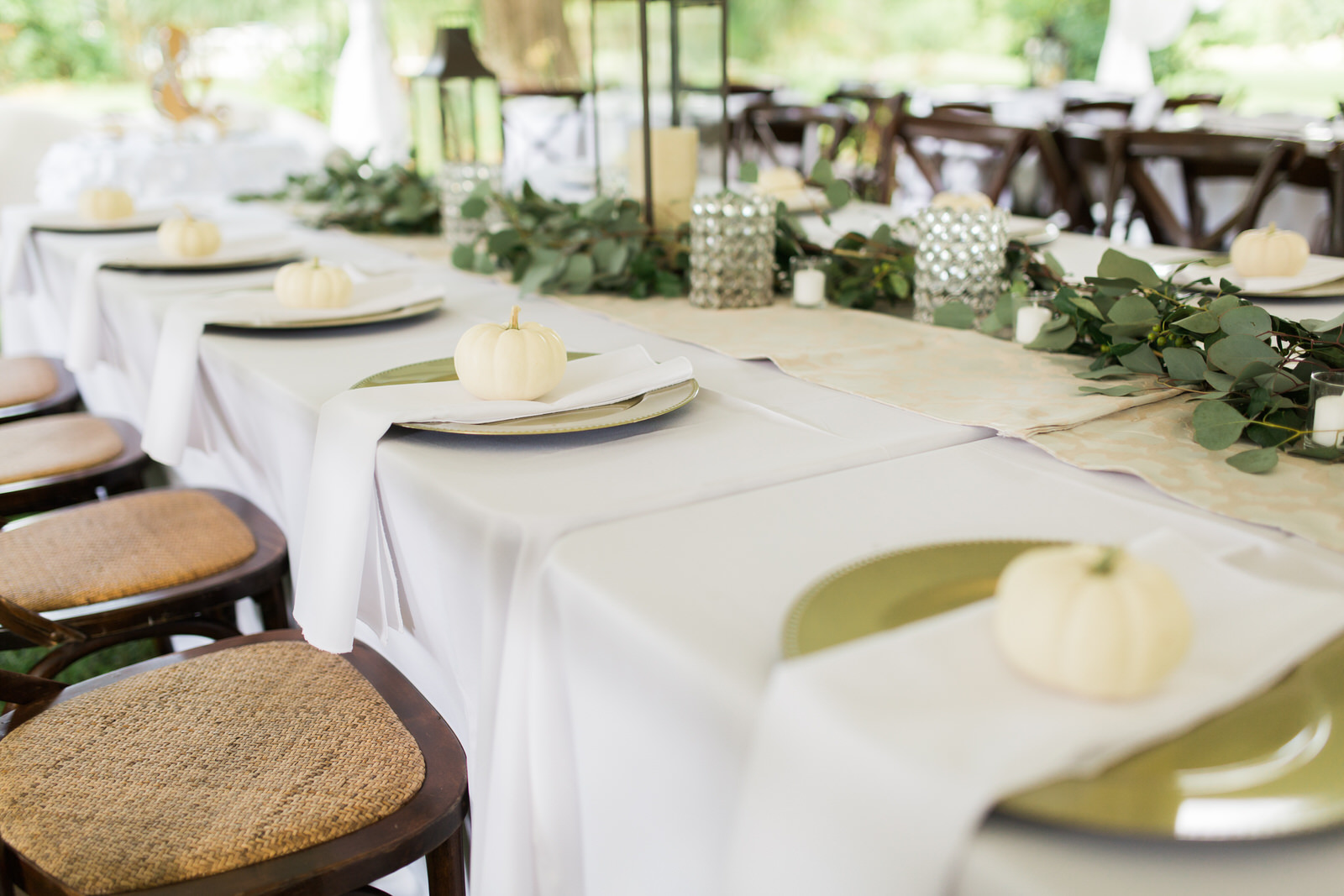 Garland and lanterns lining table for tented wedding reception, gold chargers with white napkins, white pumpkins at each place setting