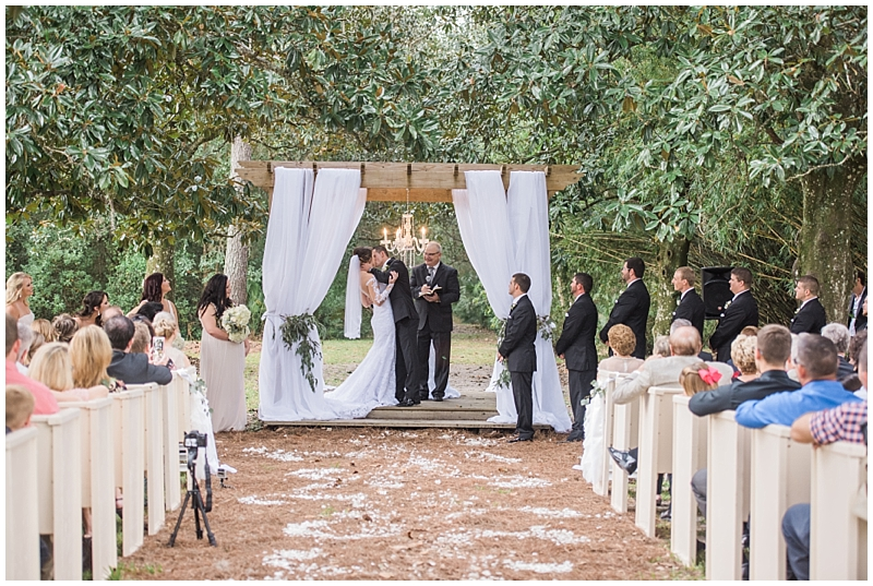 Bride and groom standing under fabric draped gazebo for outdoor wedding ceremony in Glen St. Mary, outside of Jacksonville