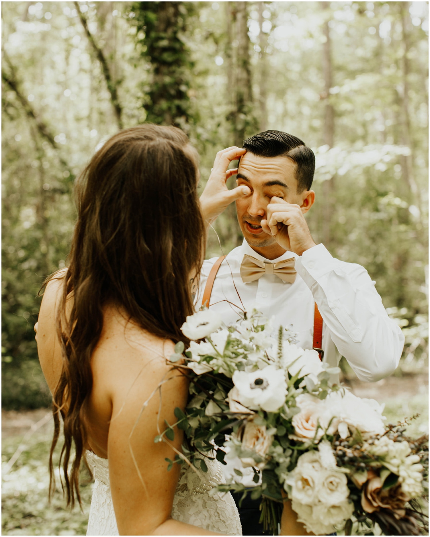 groom tearing up during their first look
