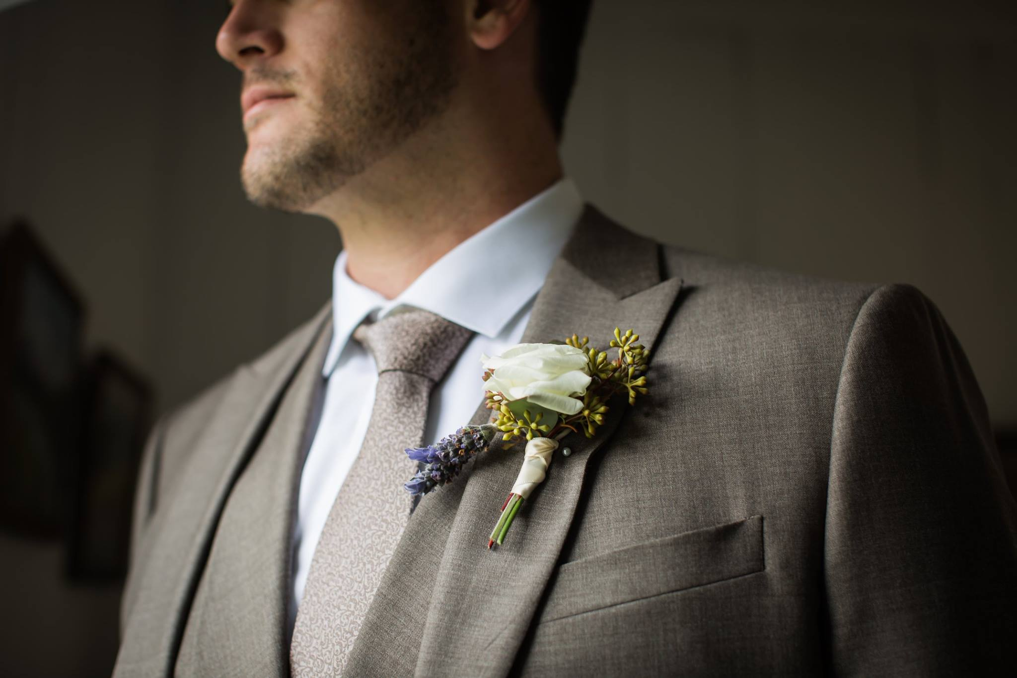 detail shot of groom's suit and boutonniere