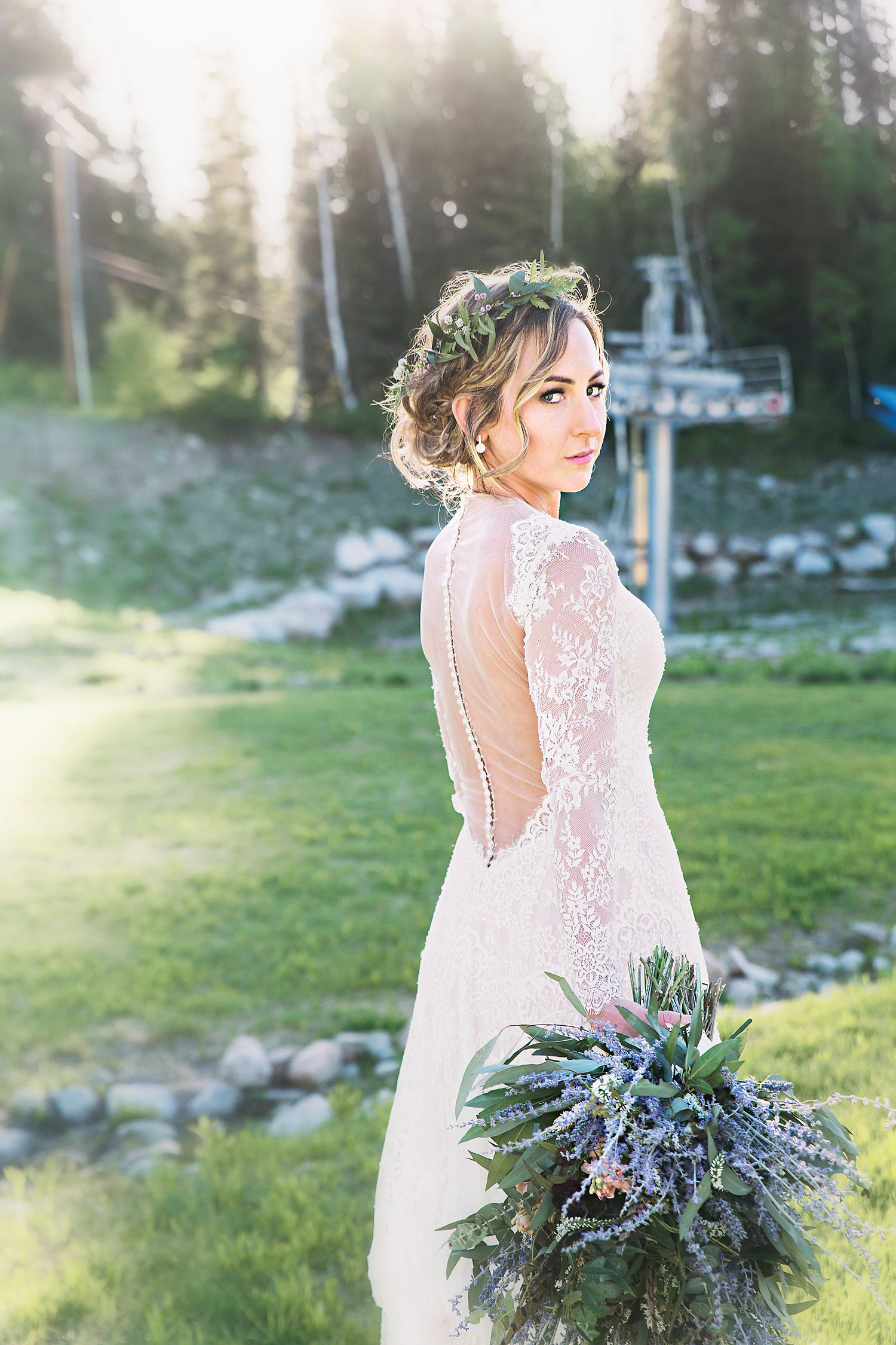 bride wearing flower crown and hold bridal bouquet at outdoor mountain wedding venue
