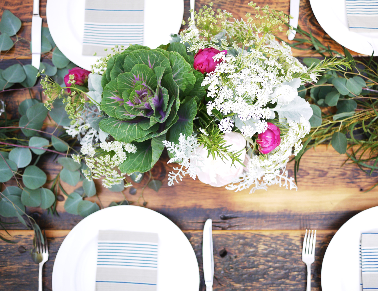 It's easy to make the floral design look great against a  Harvest Table  backdrop! This one features flowering kale, local peonies, queen anne's lace, dusty miller, rosemary, and a few varieties of California eucalyptus.