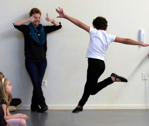 Artistic Director, Shannon Hummel, gives a thumbs up to a Ballet 1 student learning to leap!