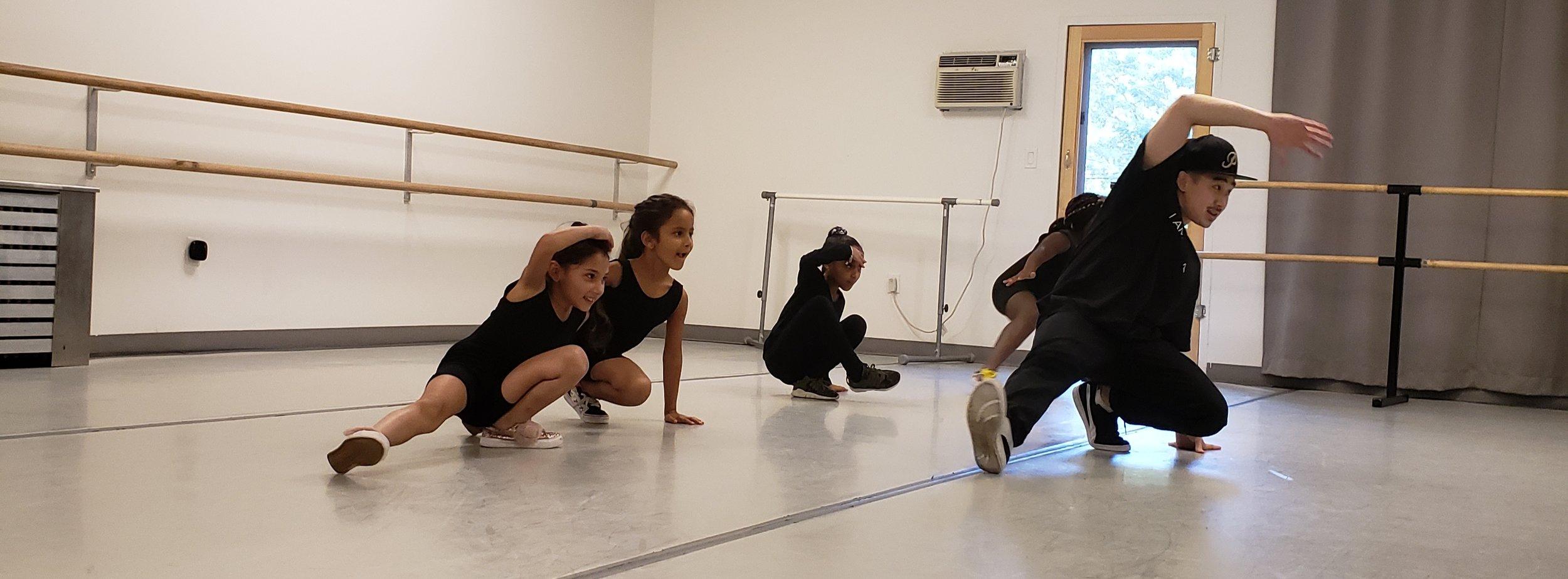 Hip hop teacher, Adam Tan, demonstrates the basics of break dancing to Level 2 students.