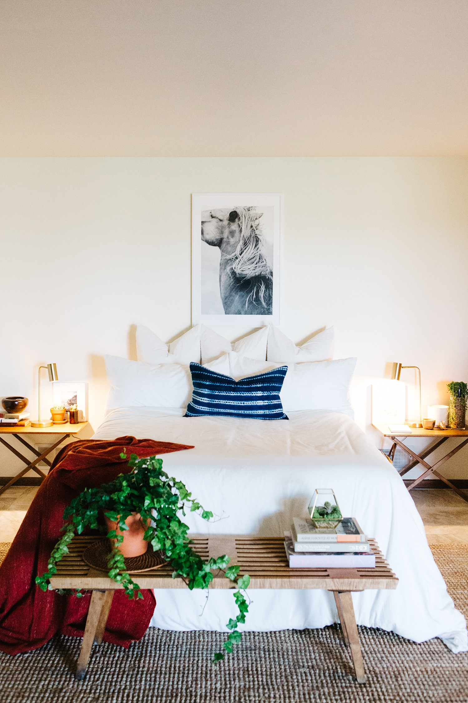 It's all about symmetry . The fine art giclee equine print anchors the mid-century bedside tables, bed, and bench together in order to draw the eye in. Forgoing a headboard keeps the space looking Scandinavian while the abundance of pillows provide a comfy Bohemian nest vibe.