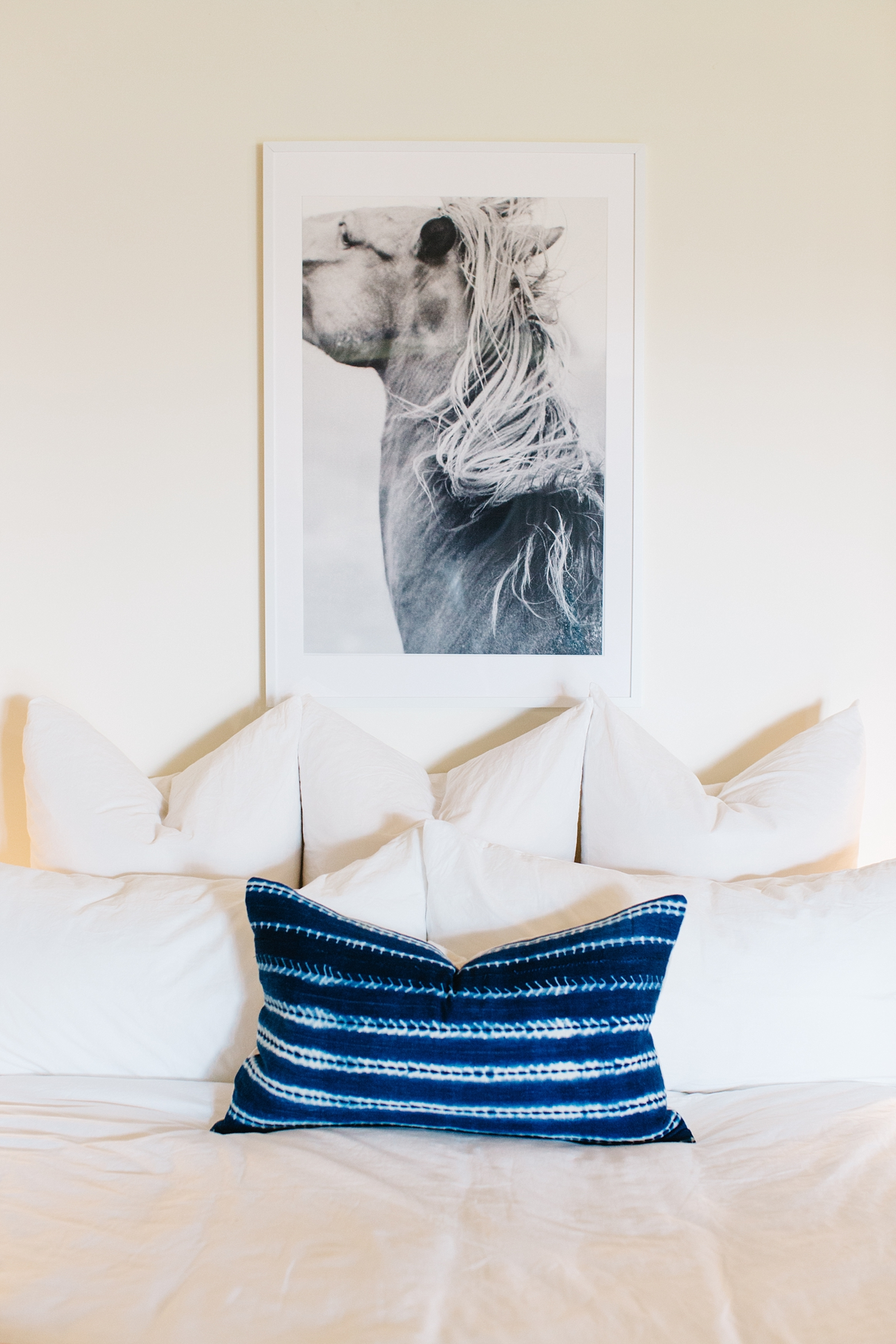 Possessing a powerful intensity,the authentic African indigo mudcloth pillow and the black and white print are the pieces I chose to really define this space. The white frame melts into the wall bringing the potency of the black and white equine print to the forefront. The strong shade of indigo of the lumbar pillow becomes an additional focal point, with the pattern elevating it to textile art.