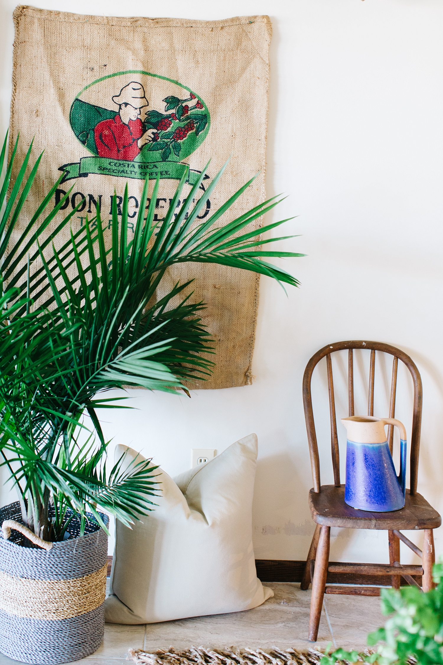 The combination of the burlap coffee bean sack from Costa Rica layered behind the fresh Palm complement the childhood chair. This colorblock clay pitcher is always ready with water to make taking care of the houseplants easy.