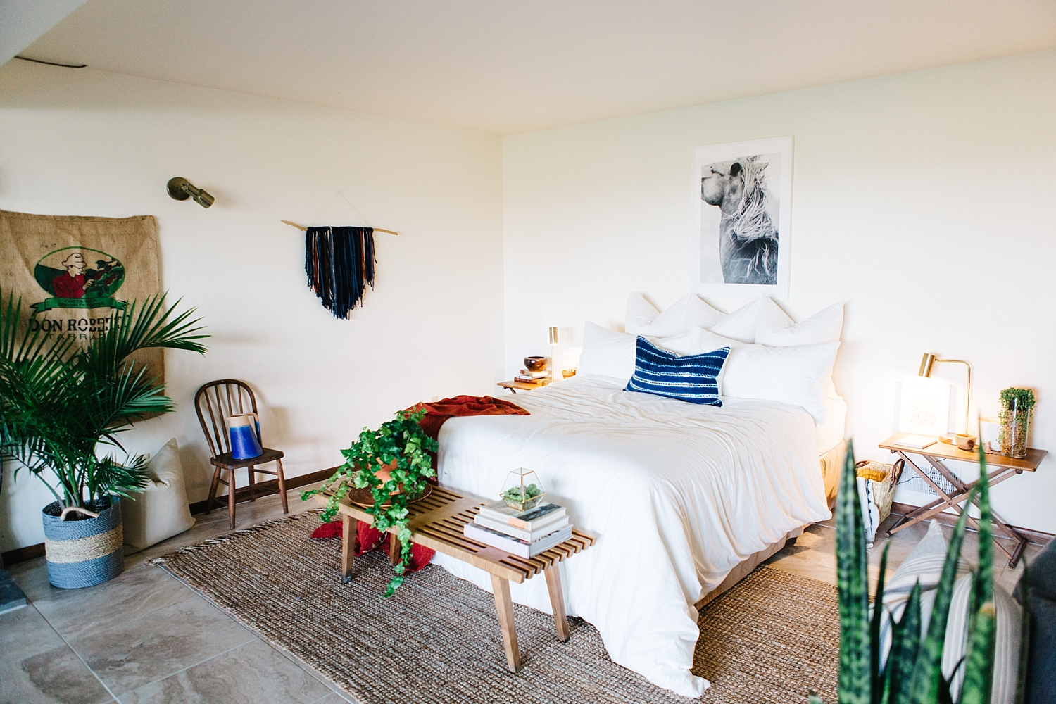 King sized white bedding on a queen size bed, houseplants, vintage furnishings, fun pops of color via textile, rugs, and beautiful art all work together to pull the Bohemian and Scandinavians styles together.