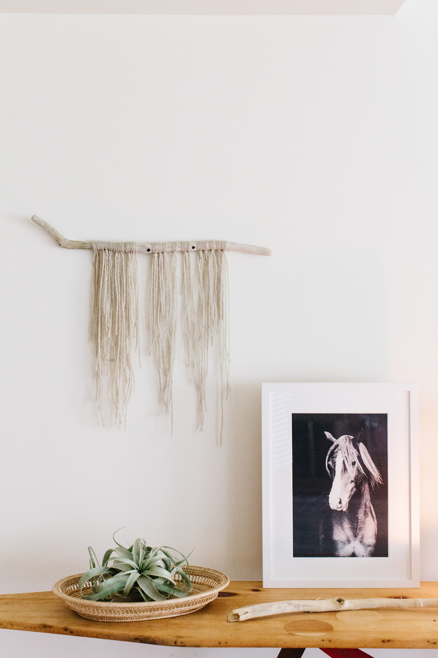 Natural wool wall hanging with beach wood.