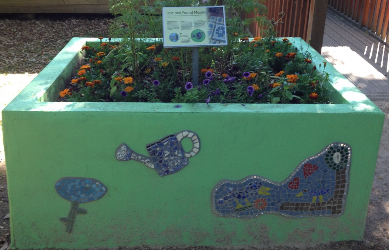 Raised bed with mosaics, including found objects in local gardens