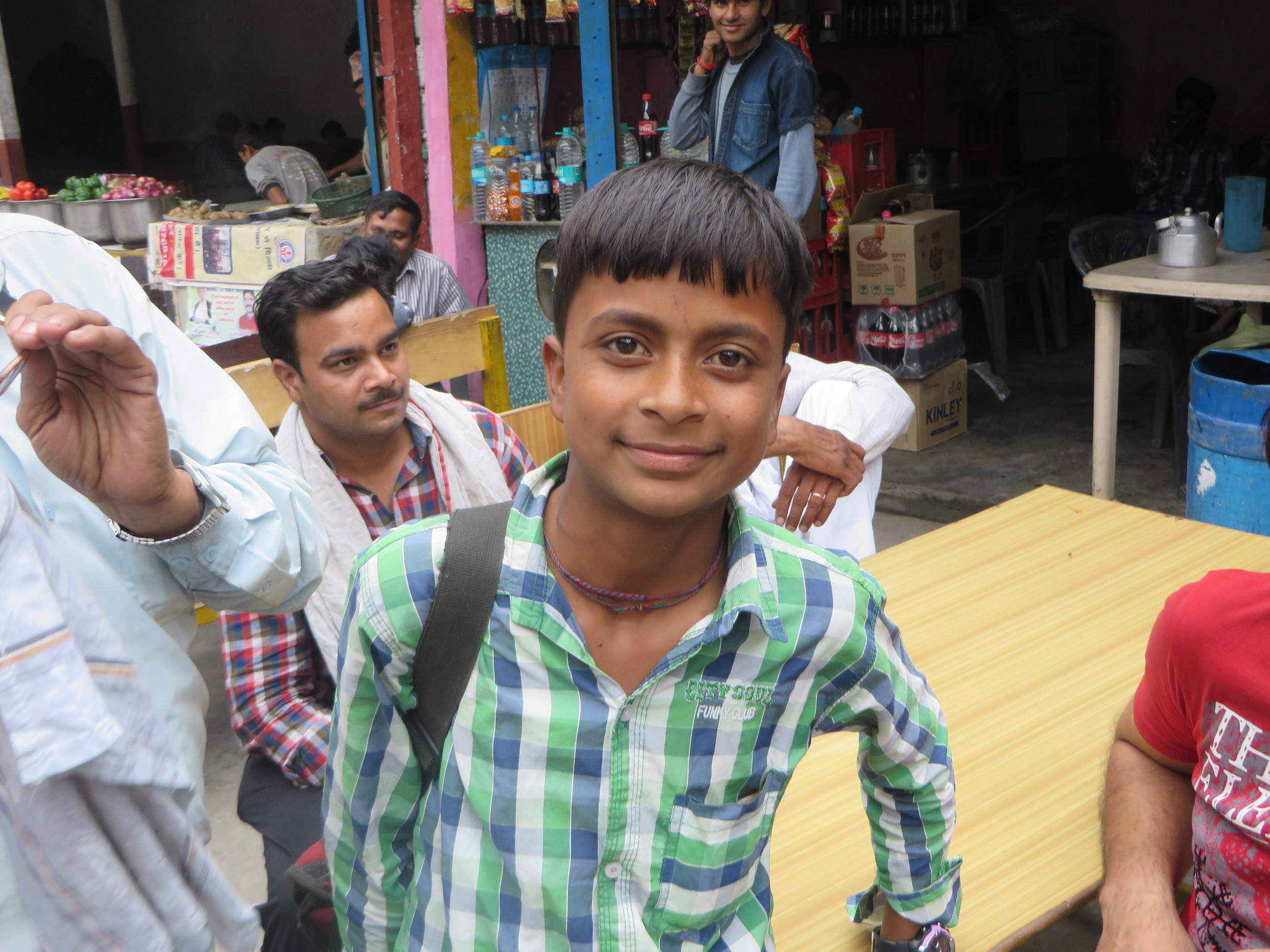 Young Indian pen-seller at bus stop on long ride to Badrinath