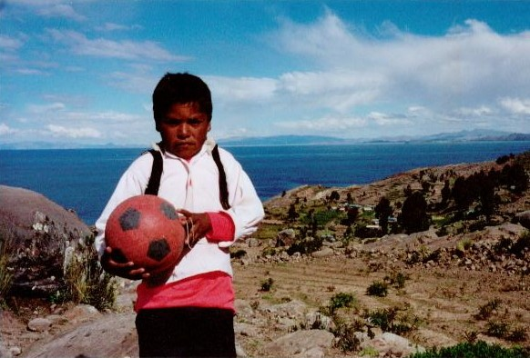 """This is Pedro, he is seven and at first did not want to share his soccer ball with me. The setting is Taquile Island, Peru - located via a four hour small-motor boat ride from Puno on Lake Titicaca. This is a magical place that has that rare atmosphere of """"time standing still."""" The island about three miles long and a mile ride is home to 2,000 hearty inhabitants who refuse cars and even electricity on the island."""