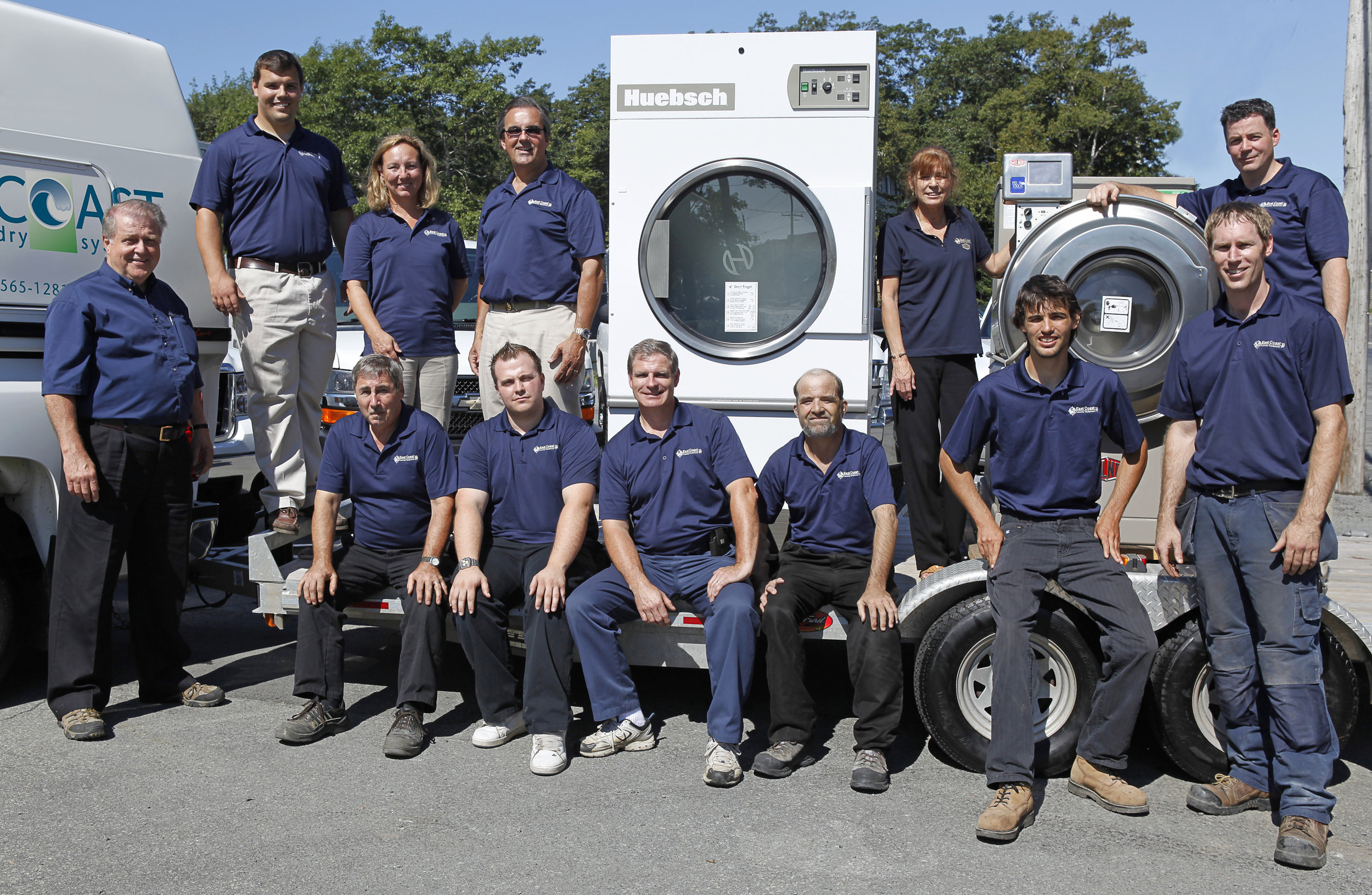 Photographed with the East Coast Laundry Systems staff are, at back row from left, Greg Blunden, his parents, Marge and Peter Blunden, and brother James Blunden, second from right in front row. Kory Orchard, operations manager for over 10 years, is at far right in back row.