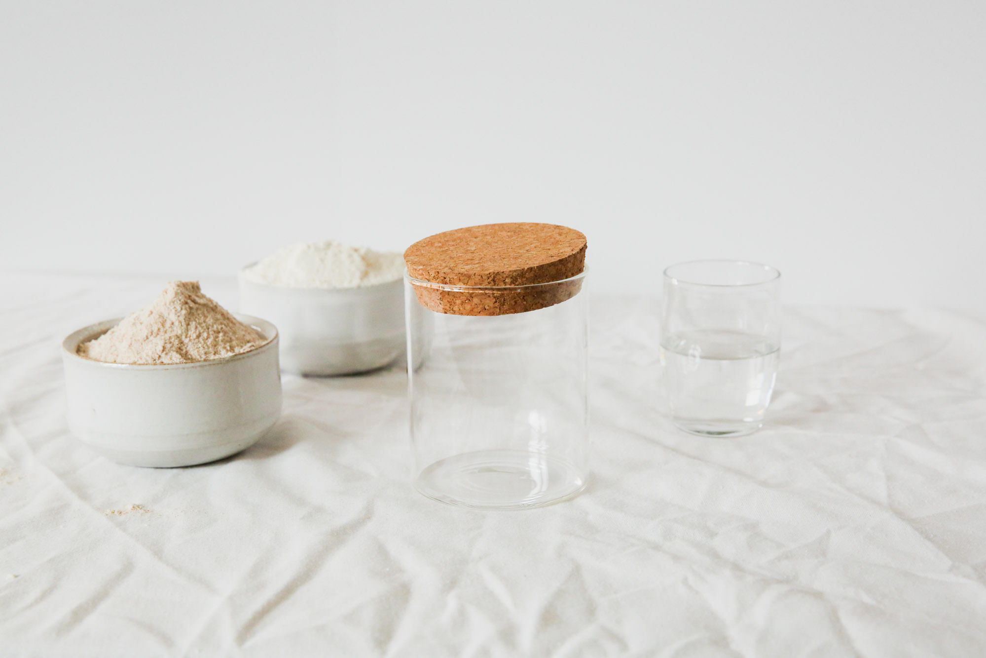 From left to right: Whole wheat flour, unbleached white flour, glass container (preferably with straight sides), water