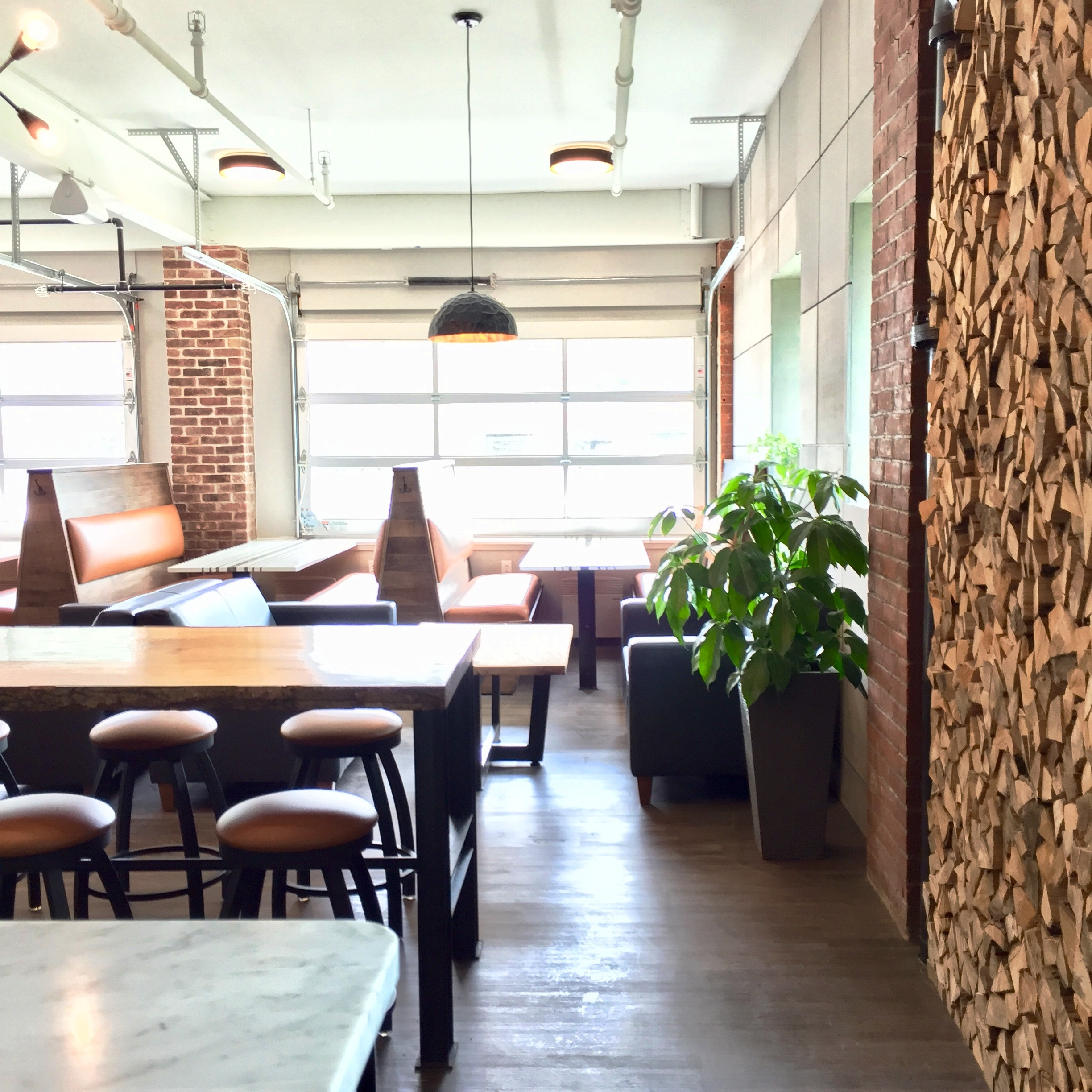 Warm local woods, metal, custom seating, marble counters, paneled walls, rustic lighting and lots of greenery…Pizza 44, Pine Street, Burlington, Vermont.