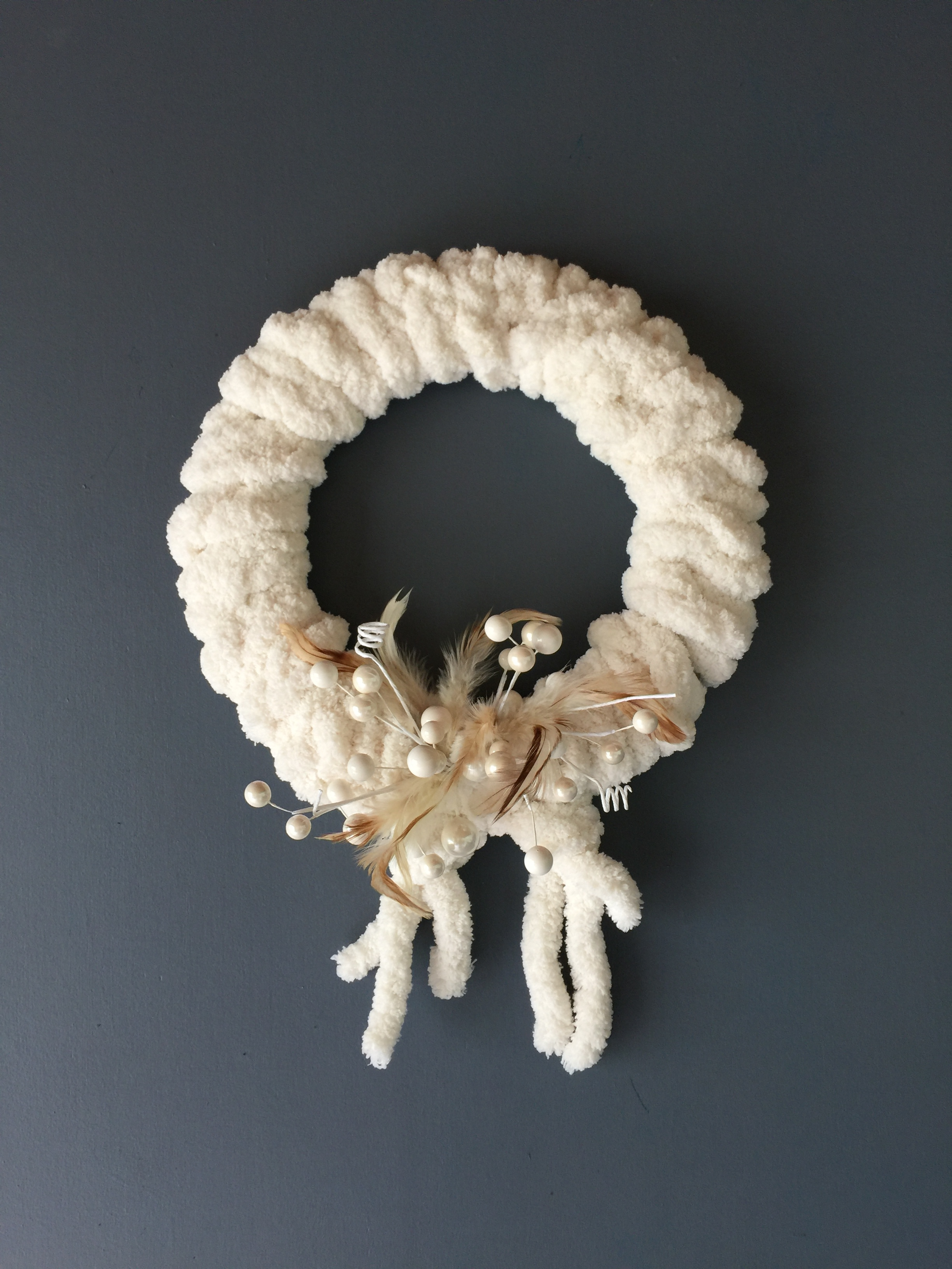 Super simple, 15 minute wreath! I had some left over fluffy yarn, a few feathers and some faux beads and I made a cardboard ring to wrap it around.