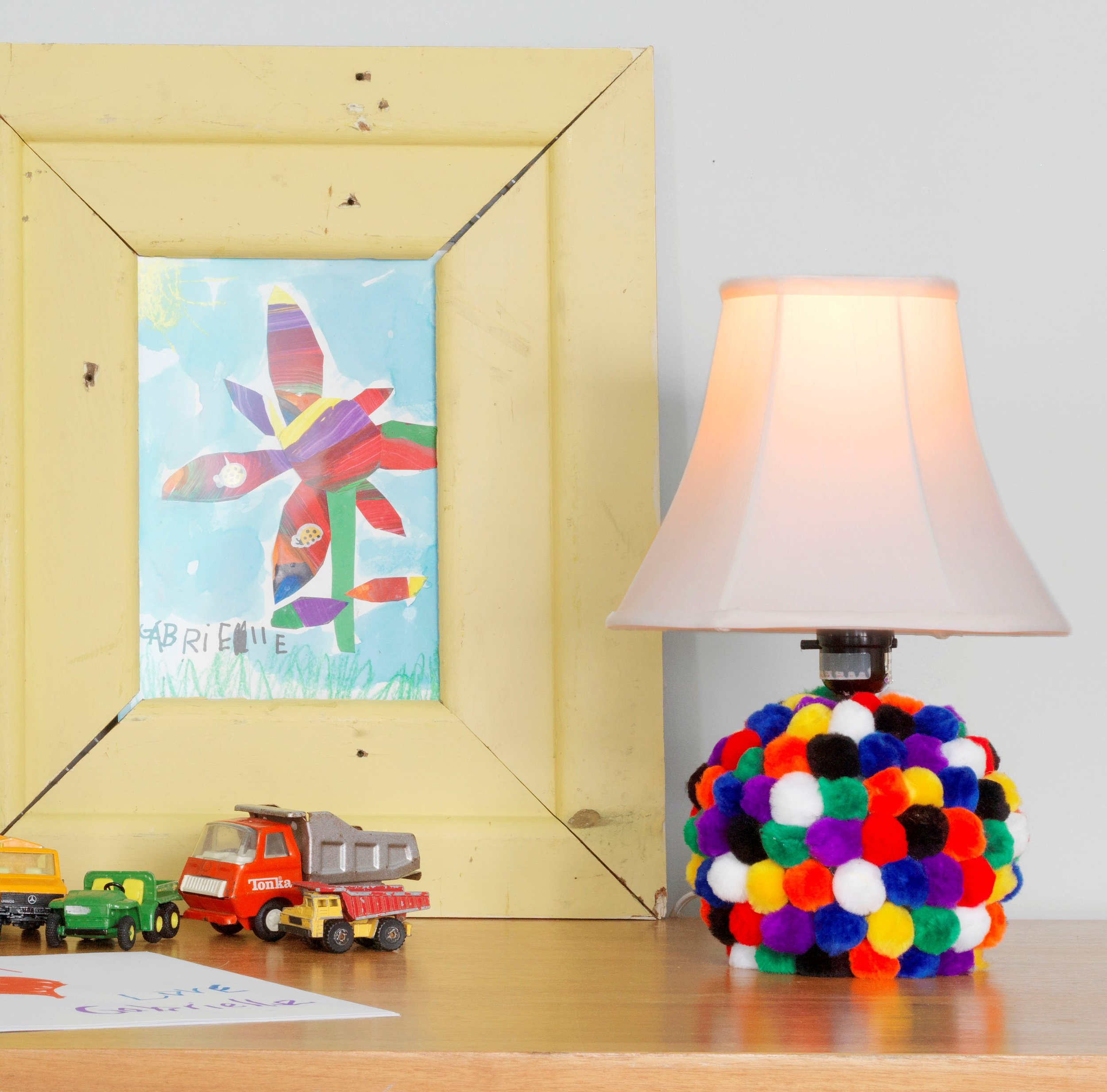 Mix a second hand store lamp with some colorful pom poms— and voilia! Instant happy lamp for the kids room!