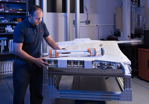 Dr. Othmane Benafan, co-principle investigator for the Spanwise Adaptive Wing (SAW) project, inspects a model of the shape memory alloy actuator and the outer wing section from an F/A-18 research plane. (Source: NASA)
