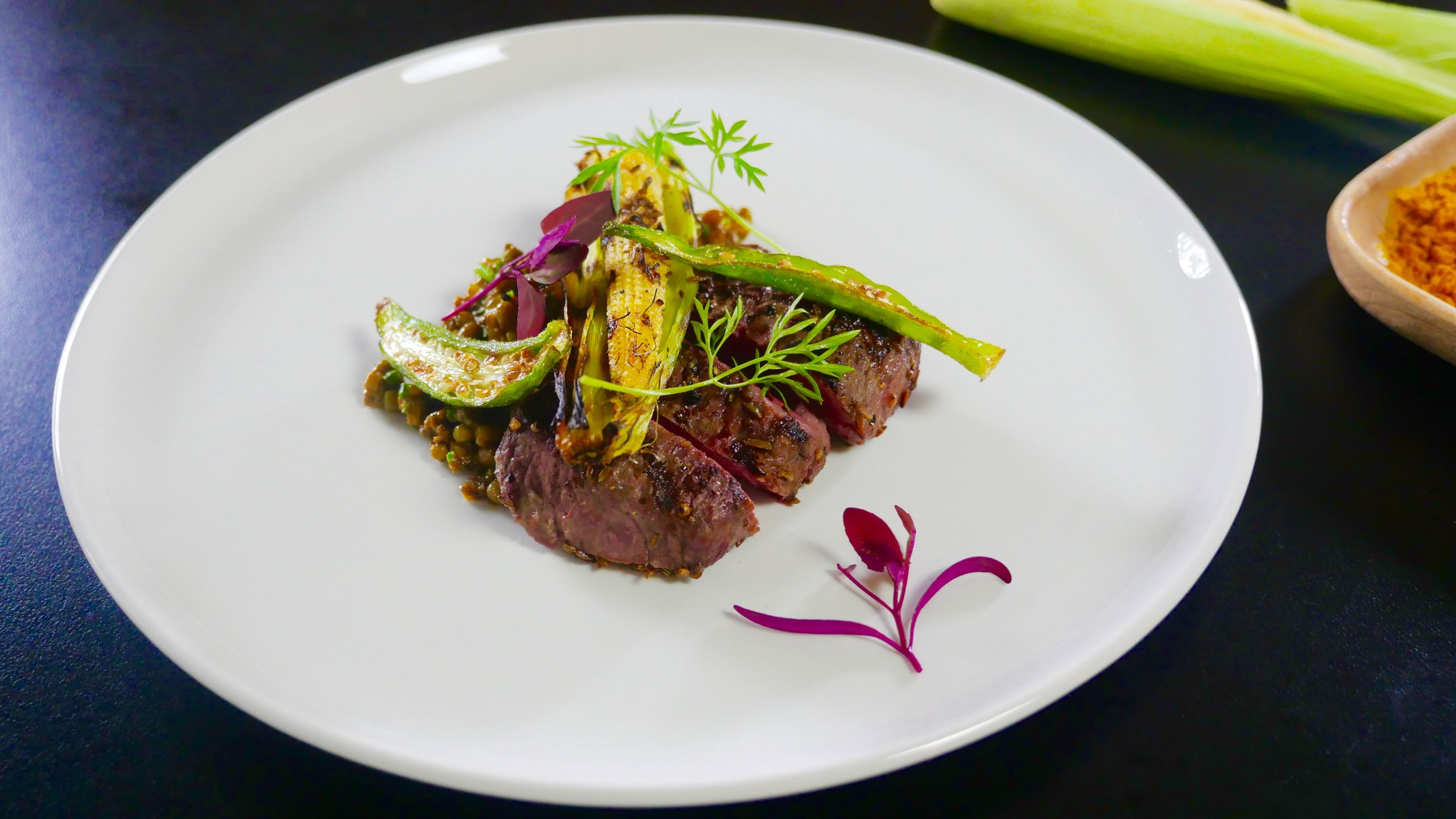 WHOLE SPICE CRUSTED LAMB LOIN, MUNG DAL, BABY CORN IN HUSK AND ORACH MICRO HERB.