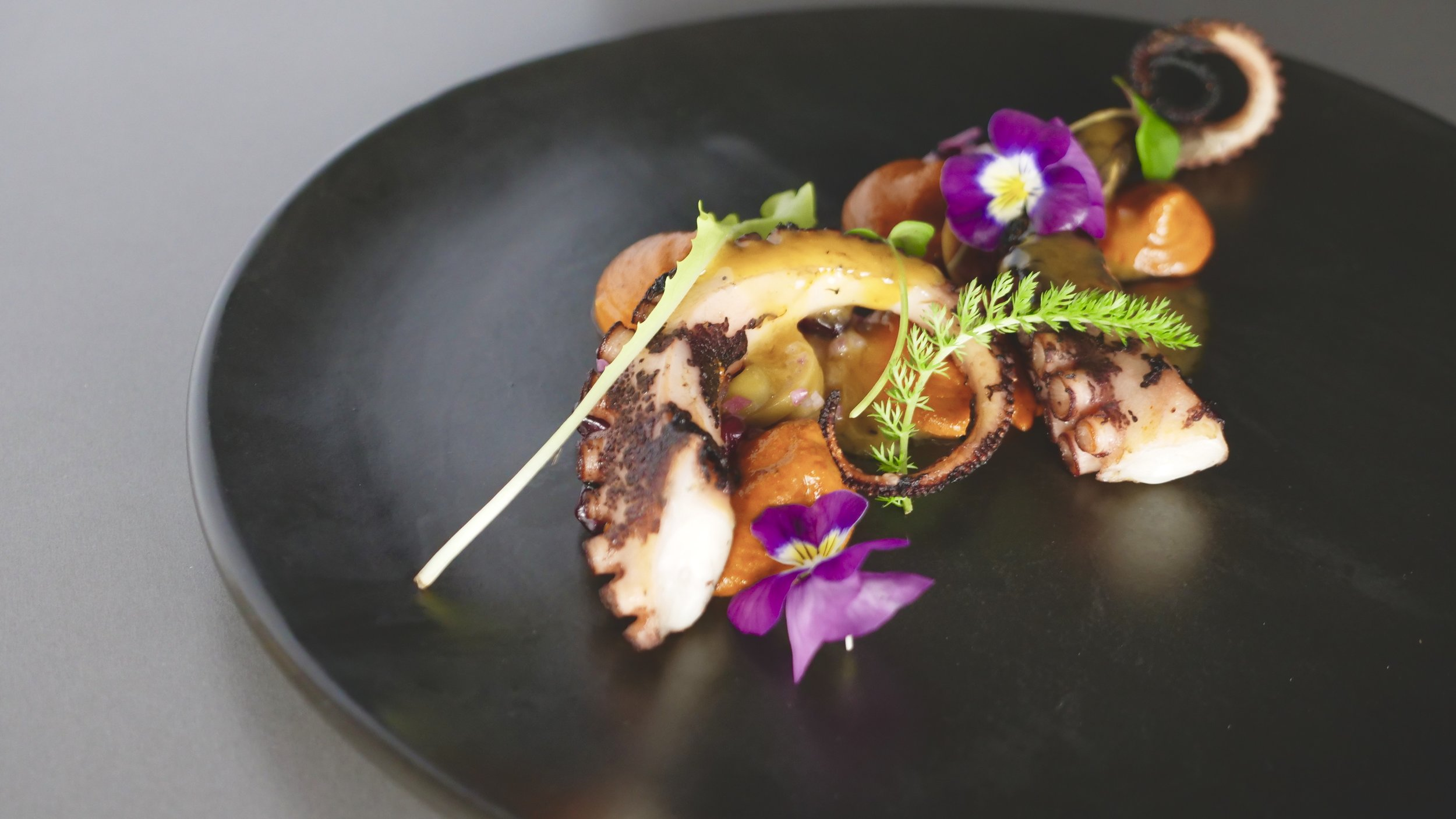 CHARGRILLED OCTUPUS, MACADAMIA, MUHAMMARA, FERMENTED SMOKED CHILLI BEURRE BLANC, GREEN OLIVE AND POMEGRANATE.