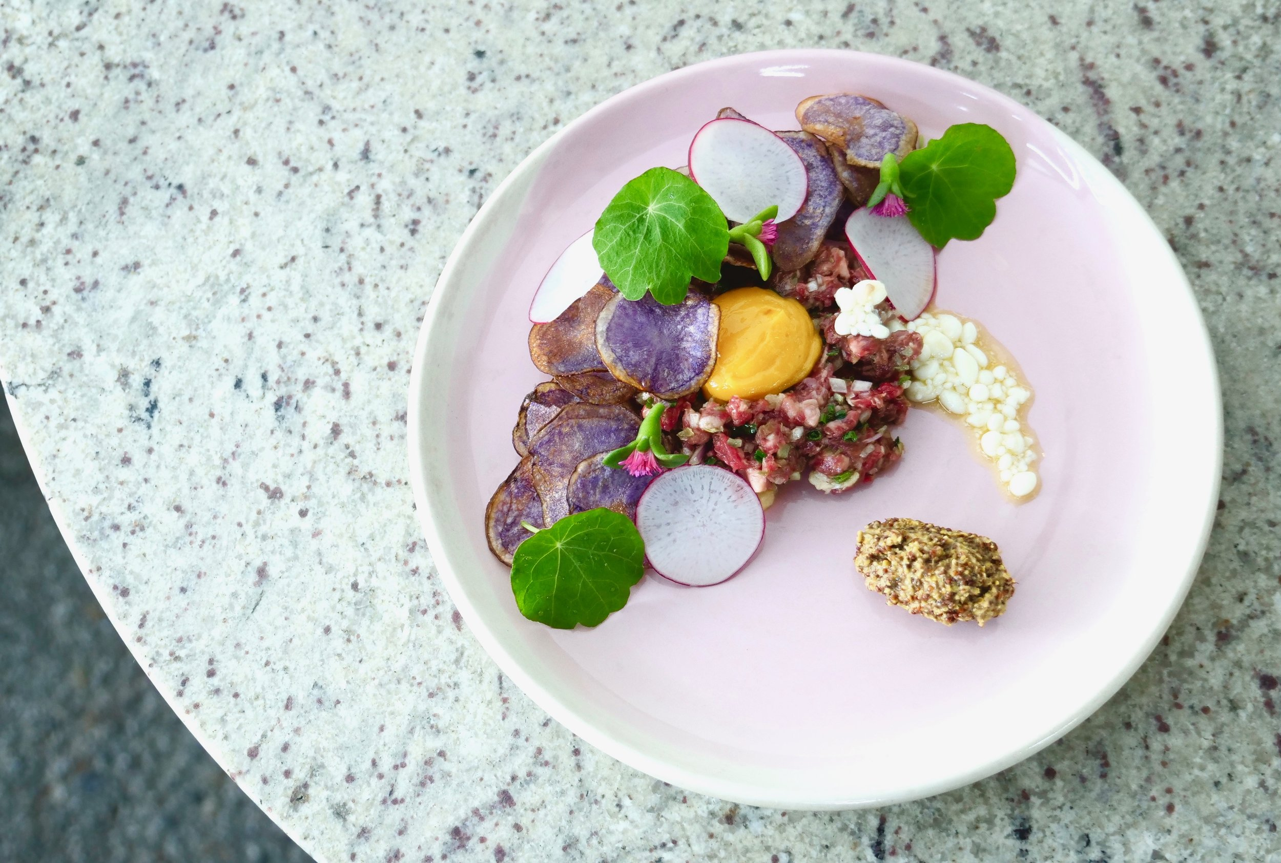 BEEF TARTARE, RED RADISH, SEEDED MUSTARD, NASTURTIUM, ICE PLANT FLOWER.
