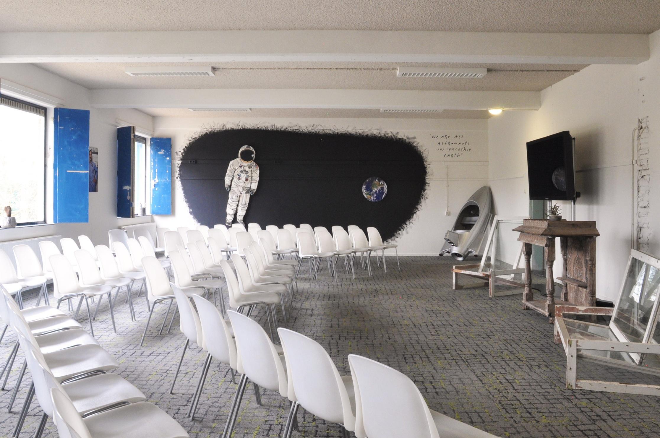 GROTE ZAAL - (OOK WEL ASTRONAUTENZAAL GENOEMD).Onze grootste presentatiezaal is gewijd aan 'het overview effect', het fenomeen waardoor astronauten allemaal als groene goeroes terug op aarde komen.Er kunnen hier maximaal 150 mensen zitten in onze prettige André Kuipstoeltjes. De zaal is 100 m2 groot en heeft veel daglicht. De huur voor een dagdeel is €750,- (voor 4 uur of deel daarvan). Voor een hele werkdag kost hij/zij/het €1150,-.Er staan standaard twee enorme LED schermen van 140 cm doorsnee. De hele zaal is te verduisteren met de ge-upcyclede deuren van de asielzoekersslaapkamers, waar ons pand 25 jaar lang tjokvol mee zat.Door een akoestisch plafond en circulaire tapijttegels* gebruiken we zelden versterking, maar op verzoek kunnen we alle denkbare audiovisuele zaken verzorgen.Standaard is de opstelling van de stoelen in de breedte van de zaal, maar met liefde draaien we ze en stellen we alles in de lengte op.Natuurlijk wordt een vergaderarrangement, lunch of aansluitend een borrelarrangement op maat verzorgd. In overleg is dineren ook mogelijk.Wil je deze zaal reserveren? Stuur een mail met de specificaties naar DOEJEDING at DEGROENEAFSLAG.nl en we sturen als de wiedeweerga een offerte terug.* Het tapijt in deze kamer is geschonken door de firma Interface. 100% Cradle to Cradle, want gemaakt van uit zee geviste visnetten.