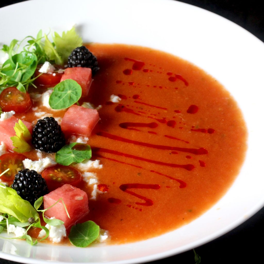 Watermelon Gazpacho - 1 (4lb) piece Seedless Watermelon, rind discarded, and chunked, reserve ¼ c for garnish1 ½ C Ice Cubes¾ C (3oz) Whole Almonds with skins3 Garlic Cloves, Coarsely Chopped8 slices day-old White Bread, crusts removed and torn into pieces2 tbsp. Red Wine Vinegar2 tsp. Kosher SaltFreshly Ground Black Pepper, to taste¼ C Extra-Virgin Olive Oil