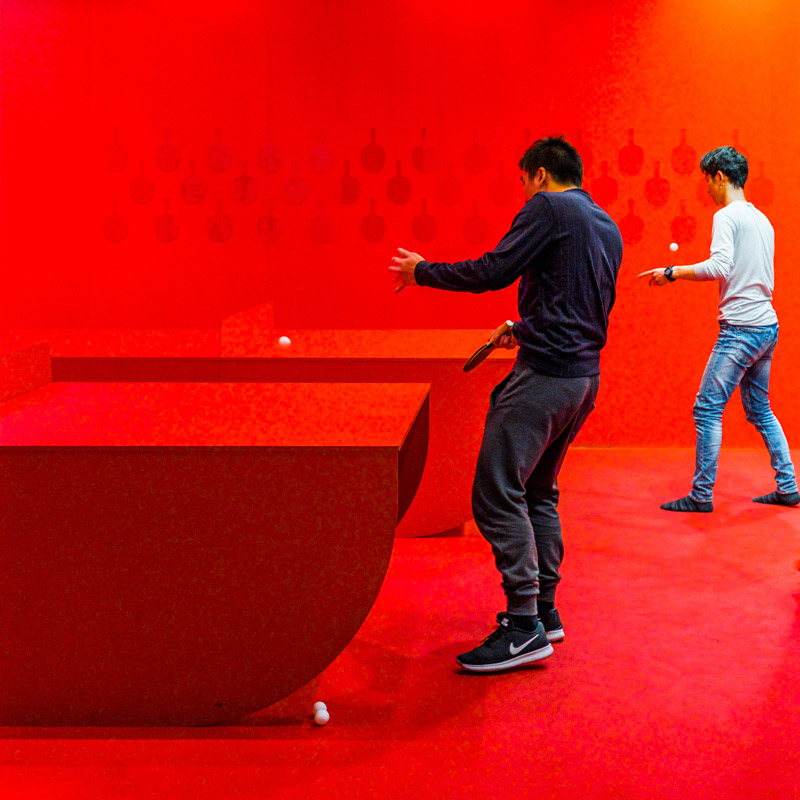 Students playing table tennis at a communal Table tennis room in a Melbourne food court.