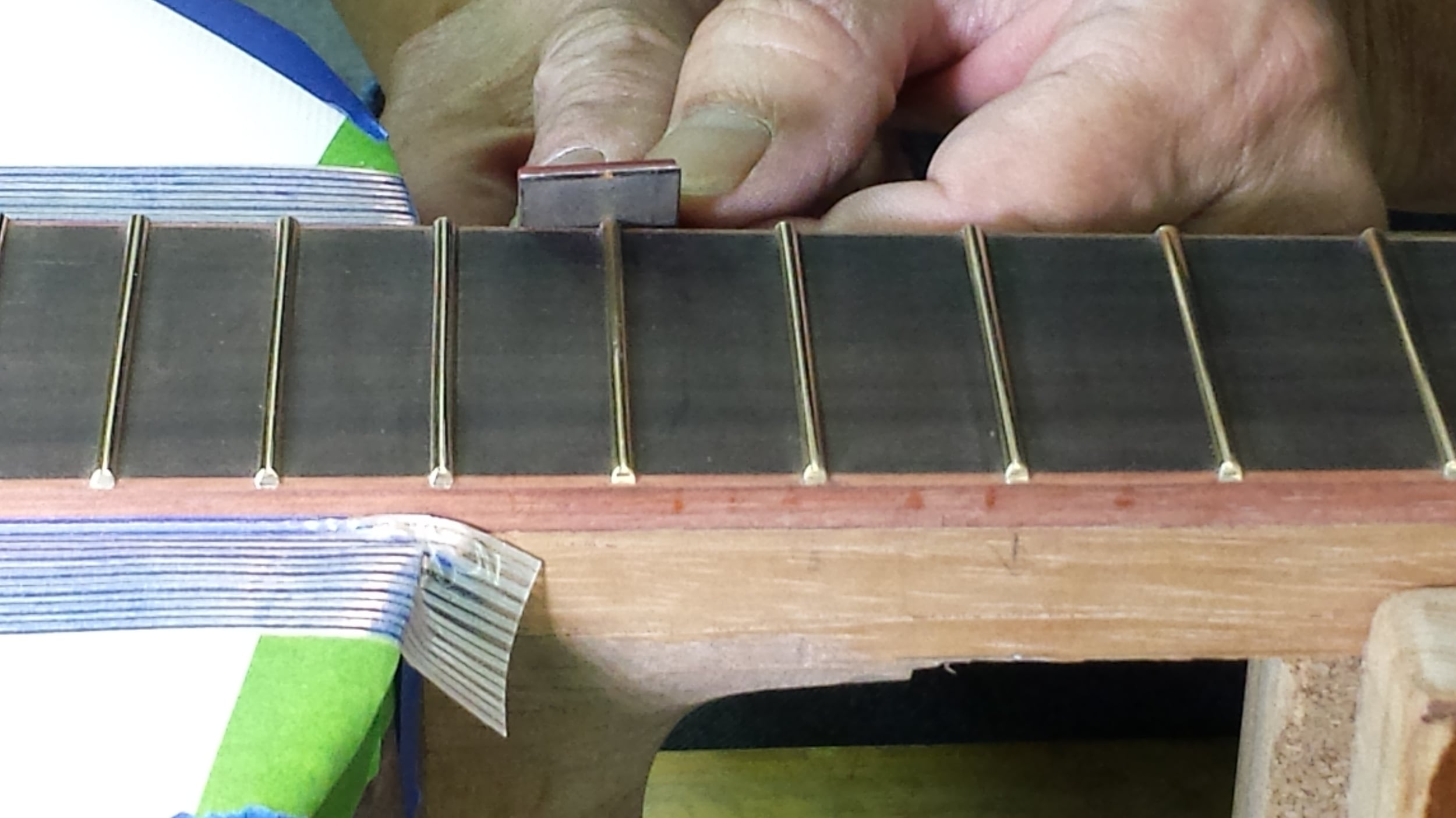 Smoothing fret bevels with a fine diamond file - Bloodwood binding on Ebony Fretboard