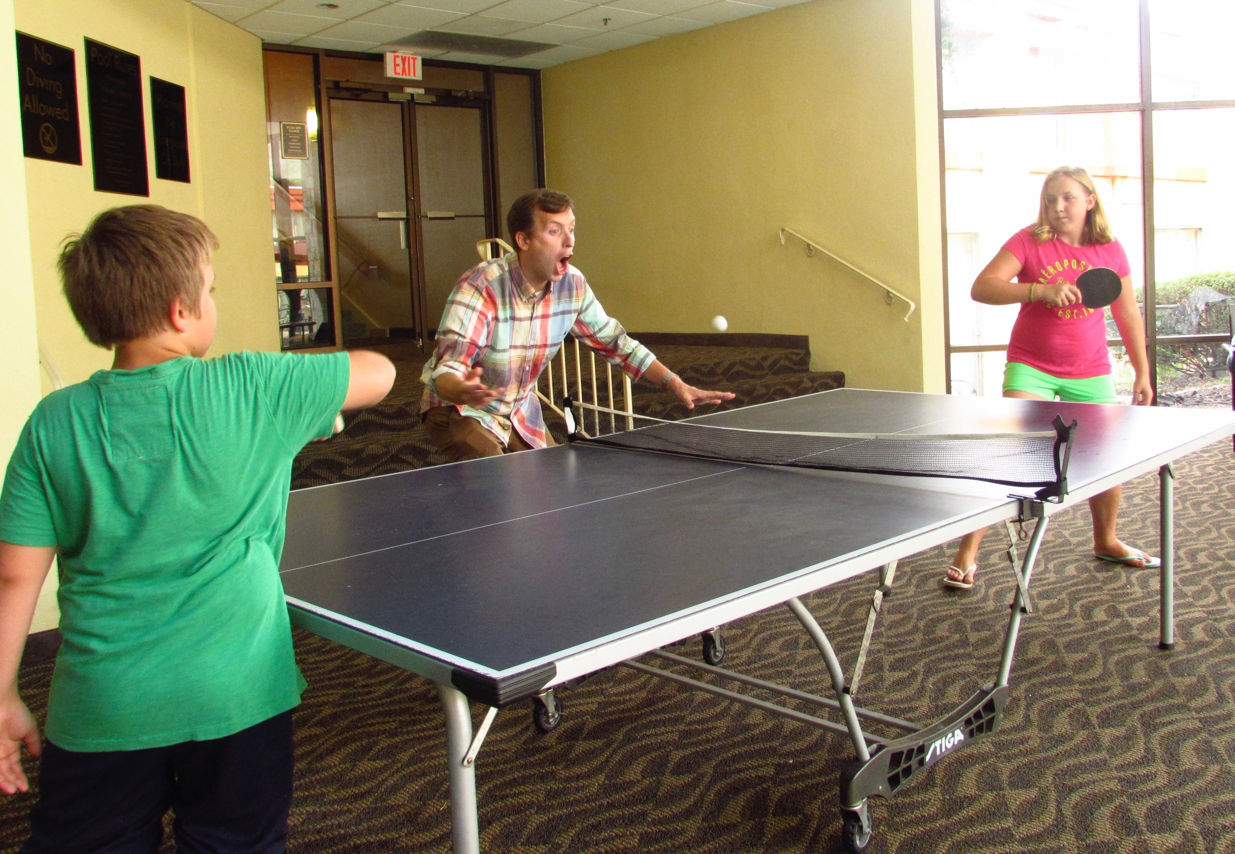 Uncle Jason referees a game of ping pong with Annie and Riley