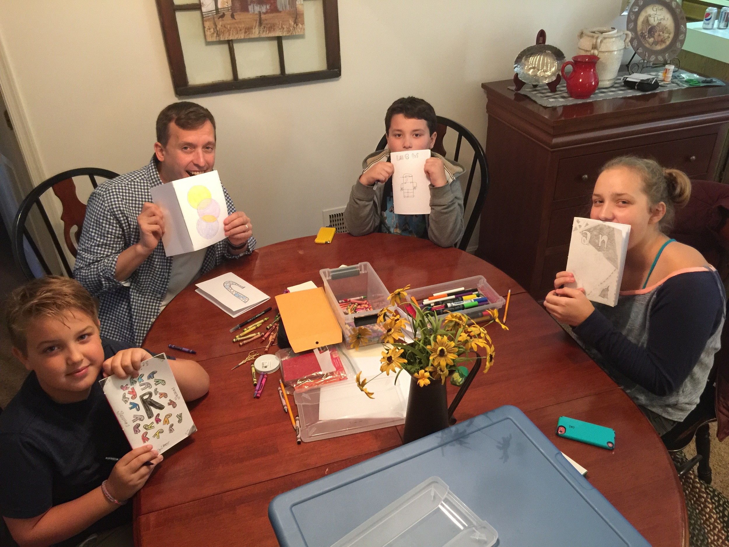 Riley, Bryson and Annie making sketchbooks with Uncle Jason