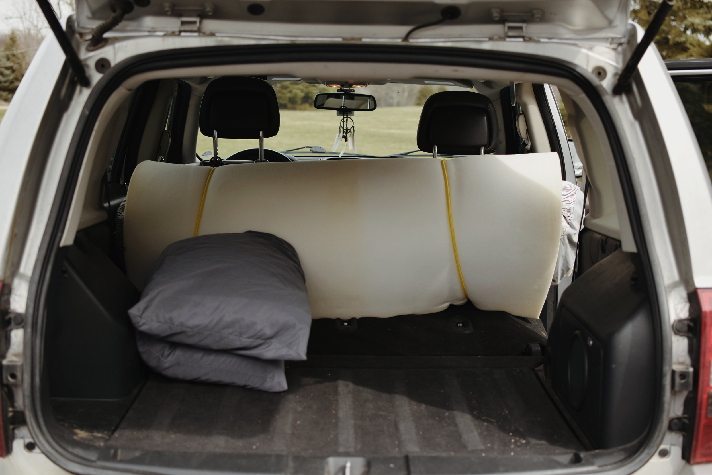 With all of my gear cleared out and moved to the front seats, I was left with a perfectly sized sleeping space for two people in the trunk of my car. I kept my bed rolled up like this for storage purposes, and to make it easy to roll out in just a few seconds.