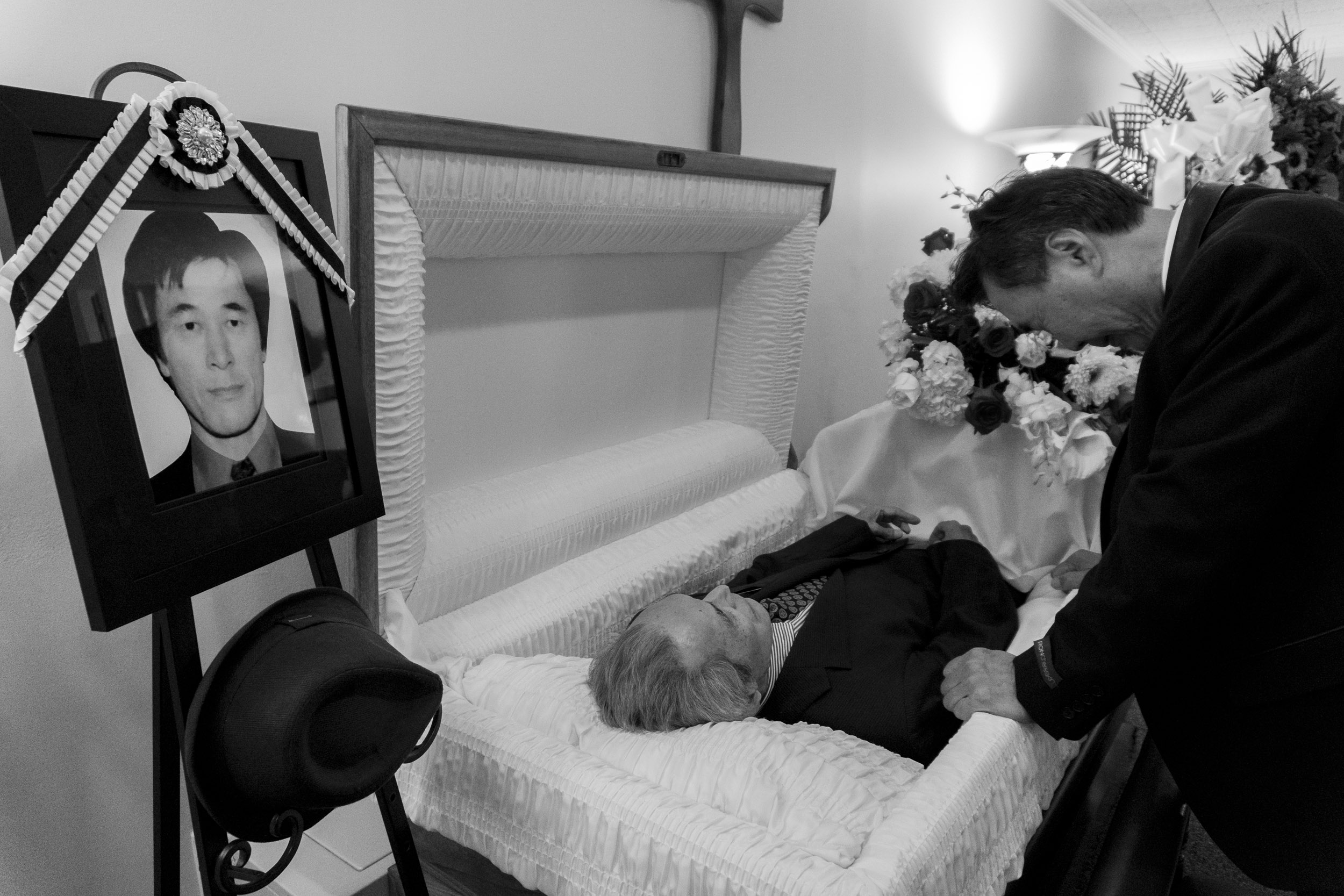 Suksoo Kim, who Chinsoo Kim had the closest relationship with out of his surviving siblings, looks at his older brother's face for the final time before the casket is closed. A picture of Chinsoo Kim looks over the scene. Chinsoo Kim died on 9/14/17 after a yearlong battle with lung cancer. September 19, 2017. Calvin Funeral Home, Brooklyn, NY. Photo by Sung Cho.