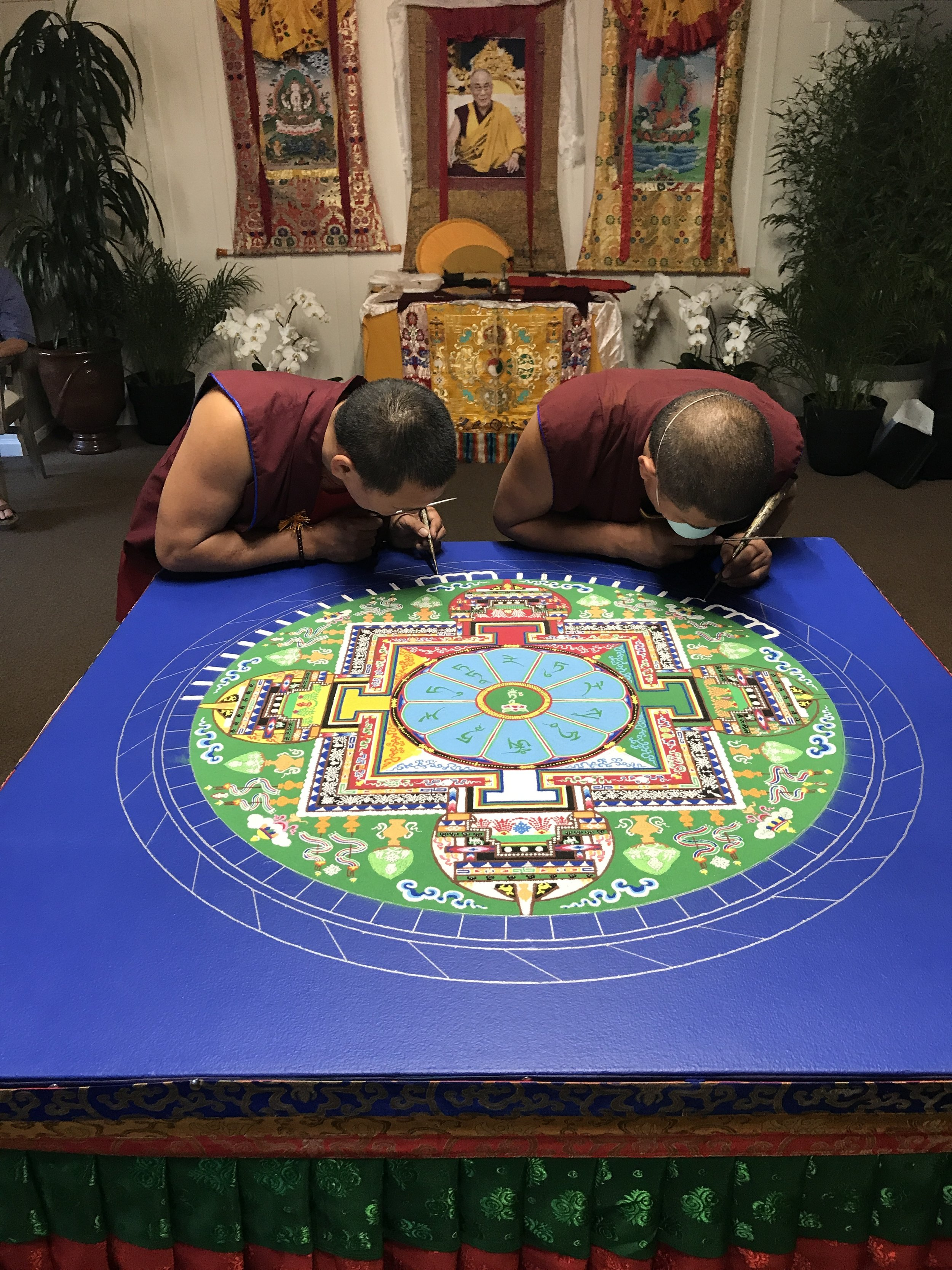 Tibetan Monks hard at work on their mandala as they reach their completion.