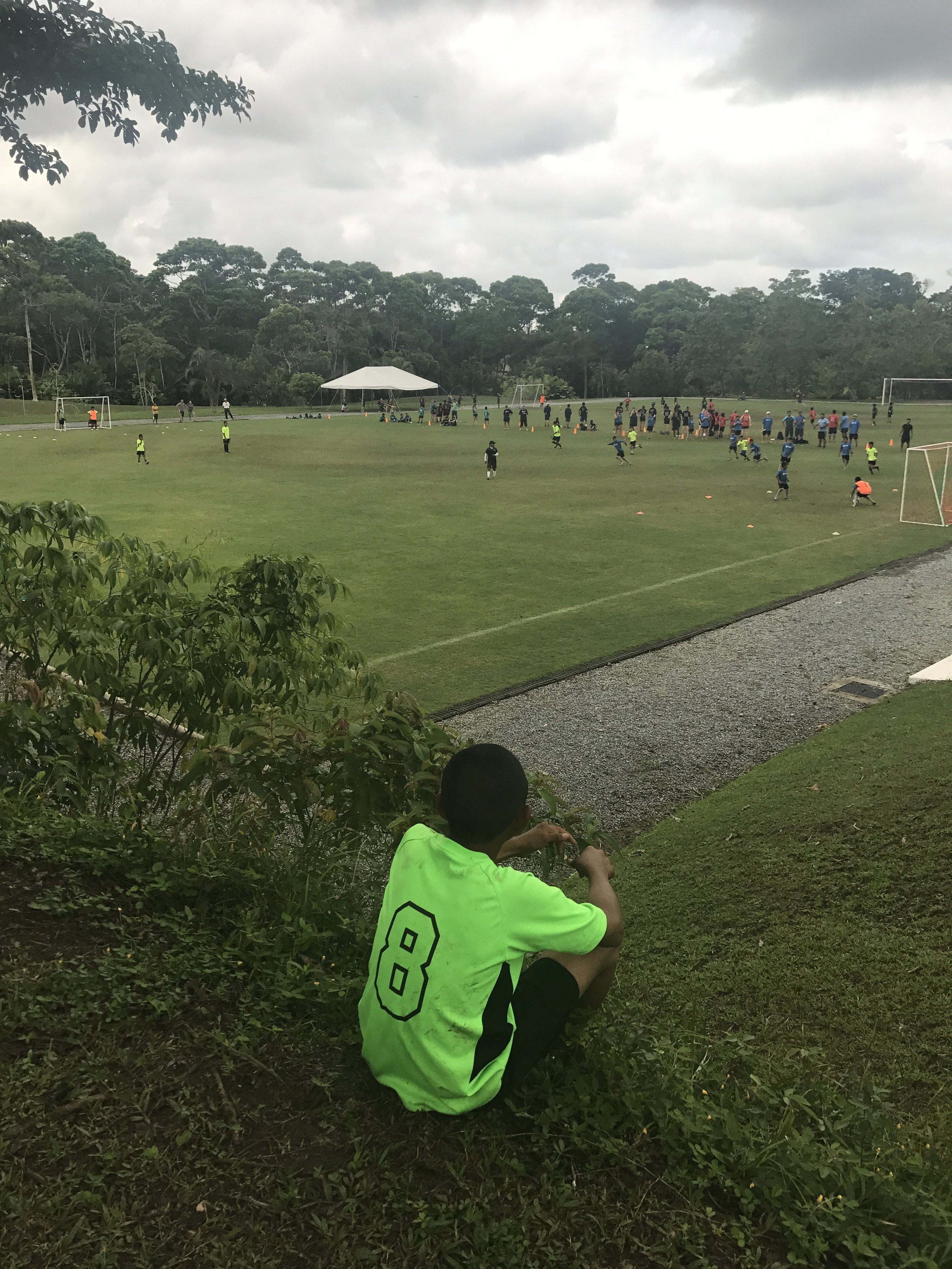 A youth watches over camp during afternoon games.