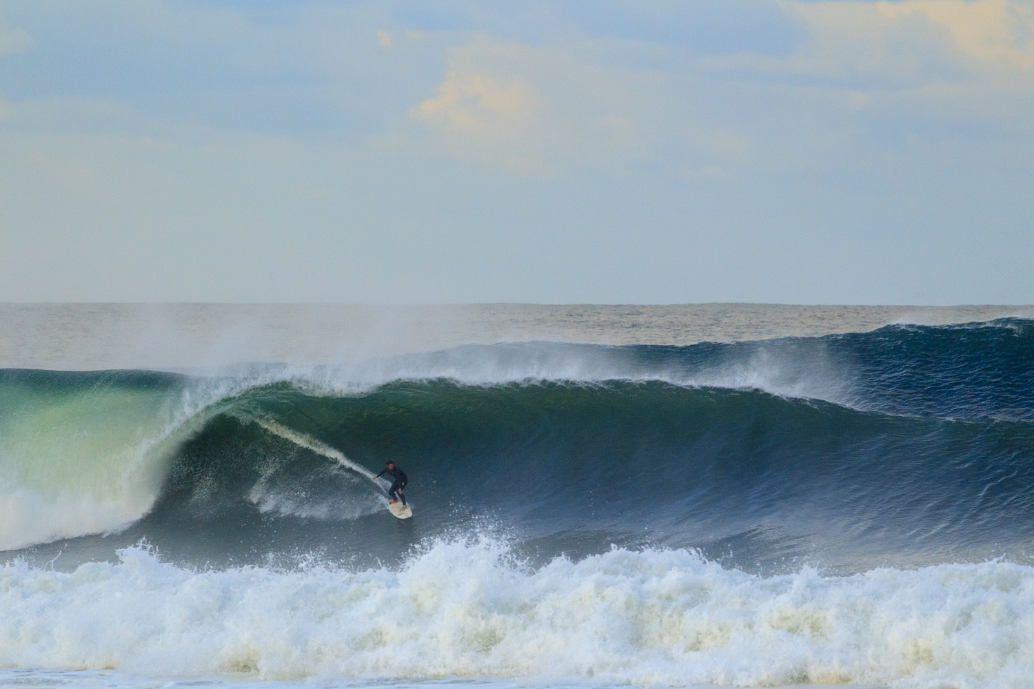 A surfer on a solid one, with an even bigger one behind.