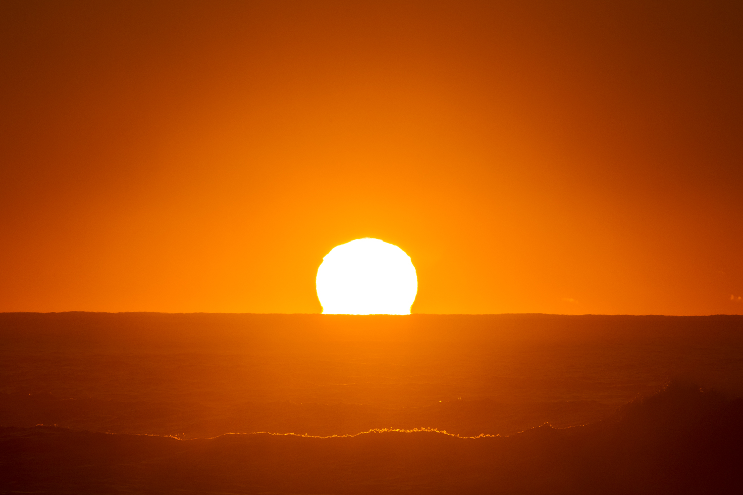 The sun peeking over the horizon, bringing life to another day of waves.