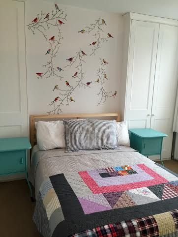 Bedroom at Wimbeldon Commons, London, England made cheery with colorful side tables, vintage style quilt and bird wall art