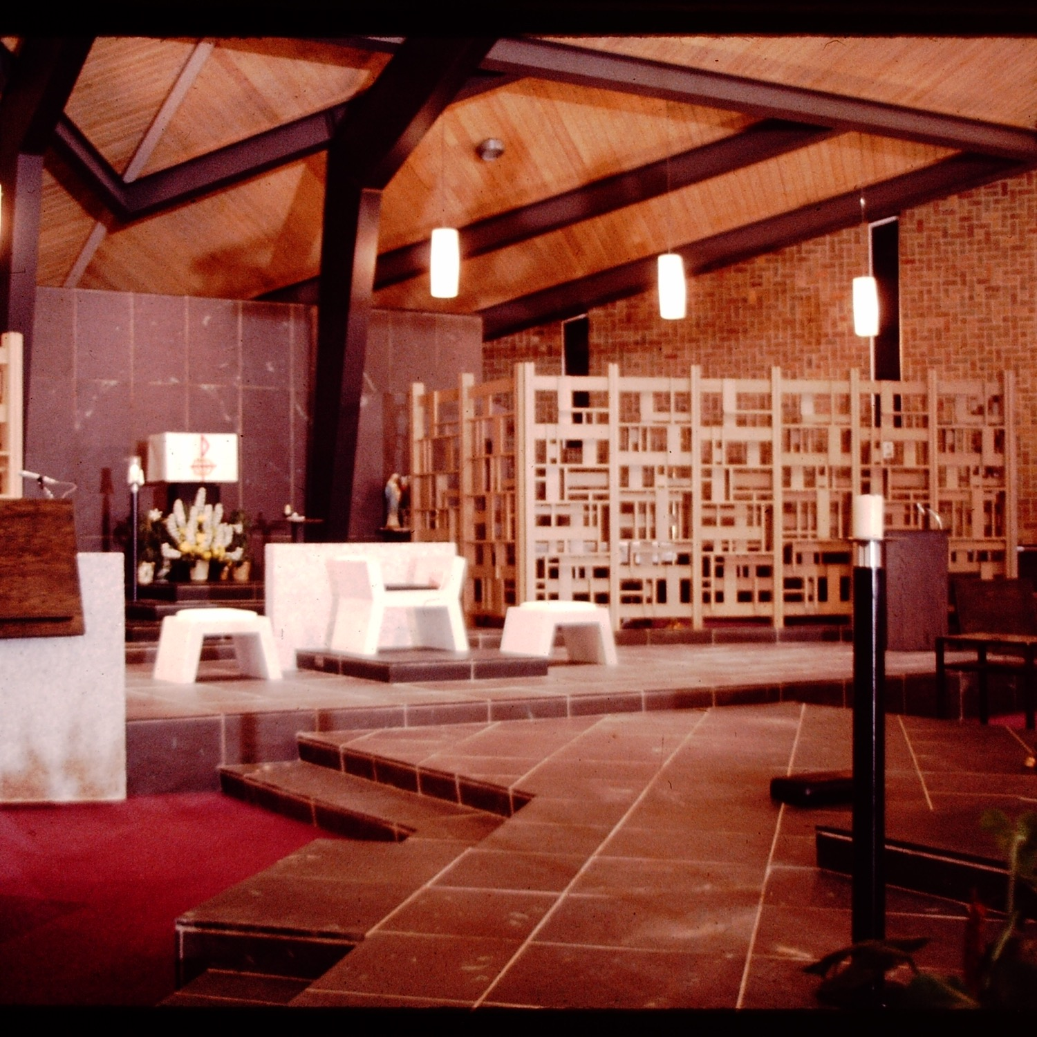 Holy Trinity Roman Catholic Church, interior view showing structural steel arches, interior brick wall,pendant lamps and alter furniture designed by Firant. Original wood screens are now gone. Slide taken at time of construction from Firant Family archives.